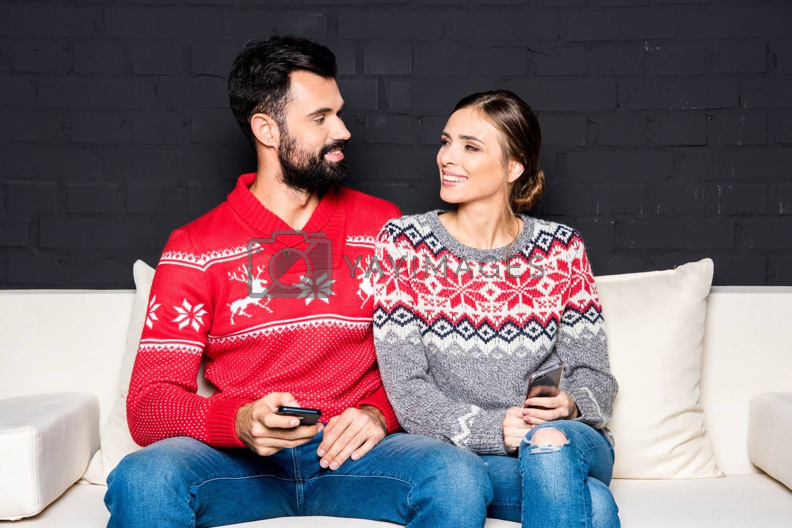 Loving couple with smartphones looking at each other while sitting on white couch