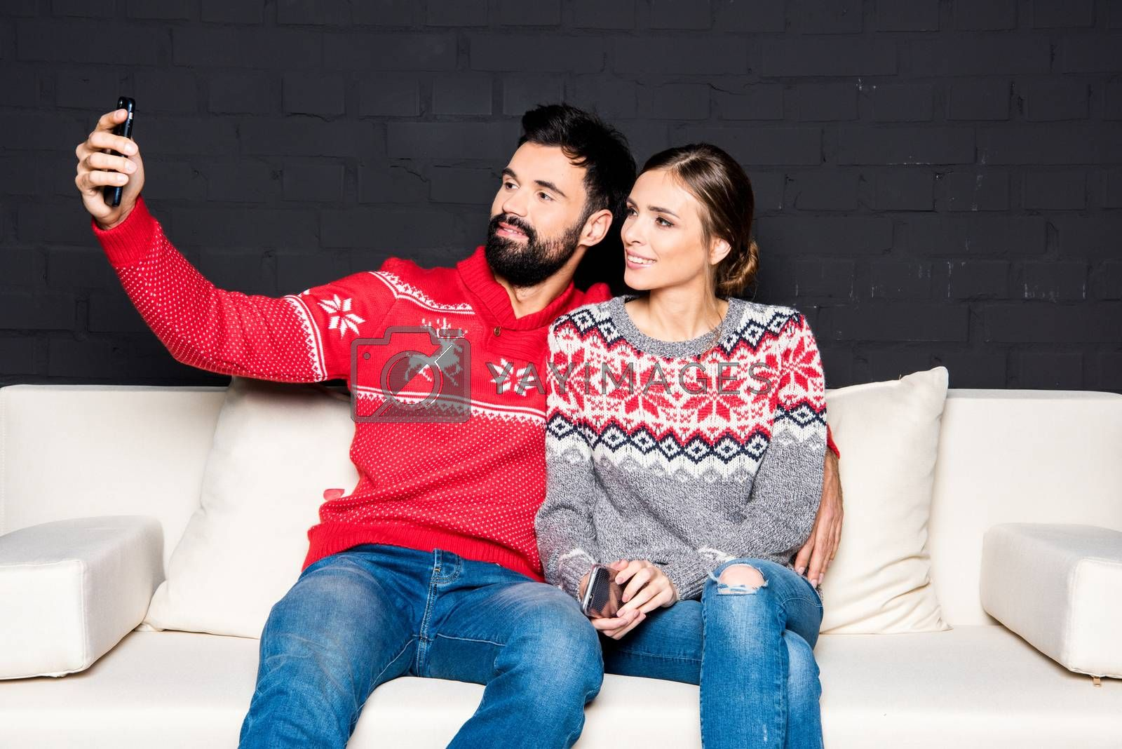 Couple in colorful sweaters taking selfie while sitting on white couch