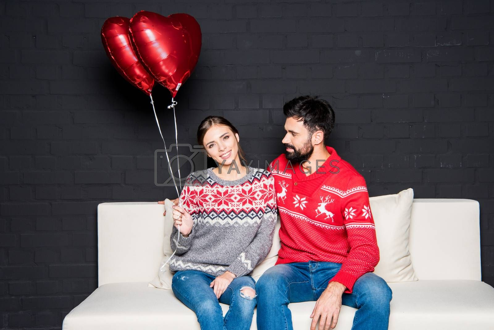 Royalty free image of Couple with red hearts balloons by LightFieldStudios