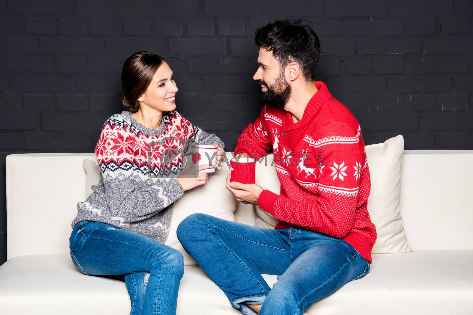Happy couple drinking hot tea while sitting on white couch