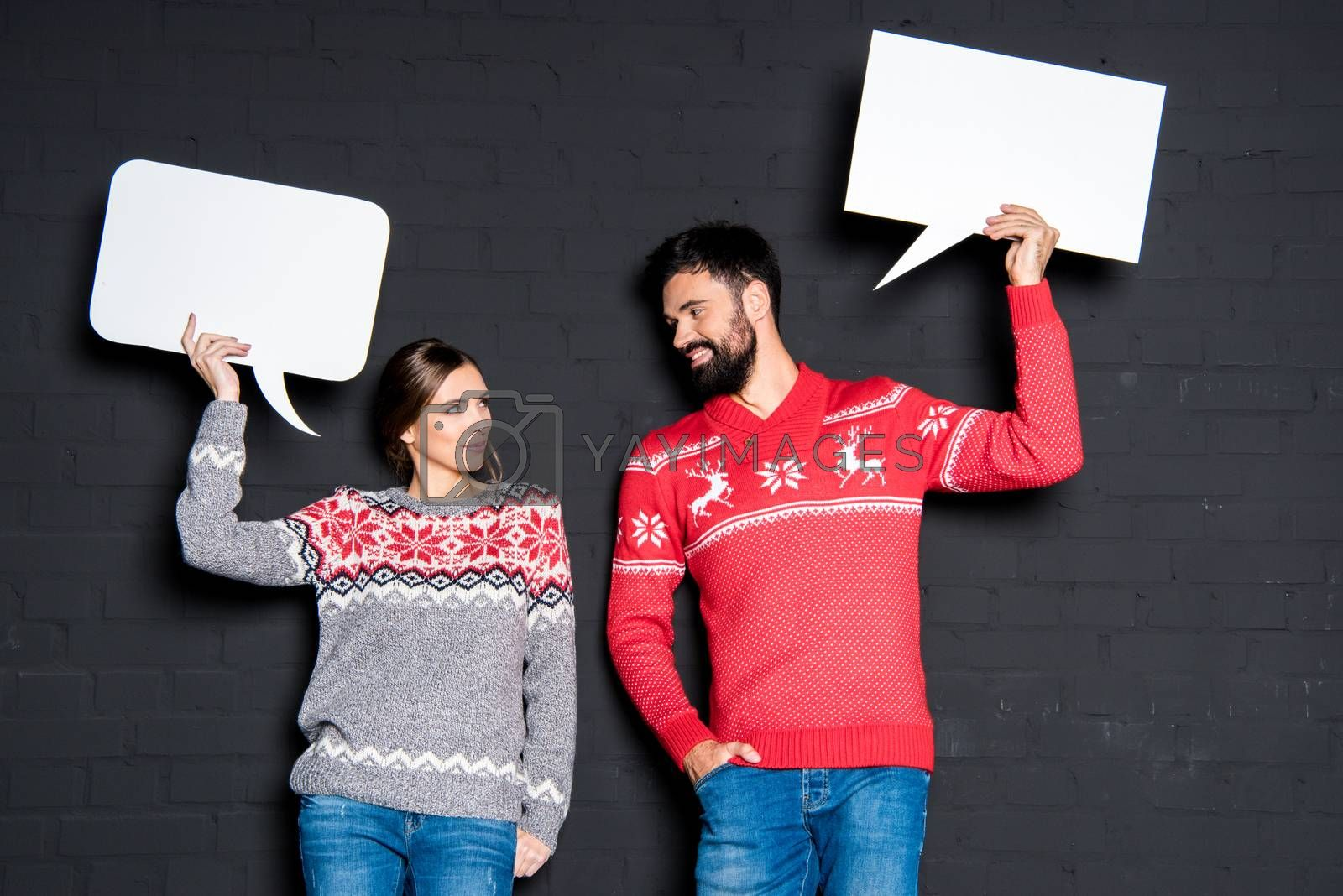 Attractive couple holding blank speech bubbles in hands