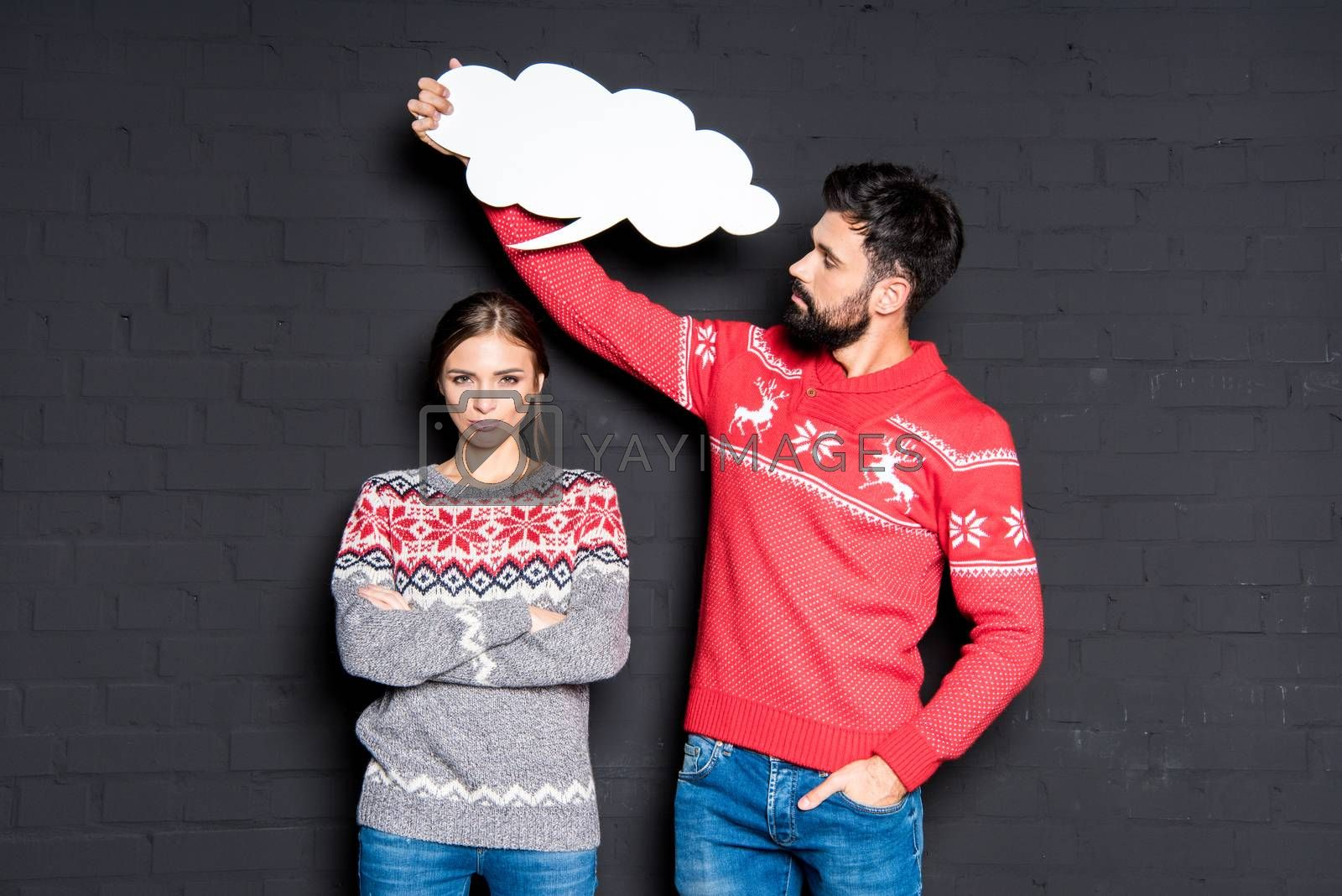 Royalty free image of Man with speech bubble over girlfriend's head  by LightFieldStudios