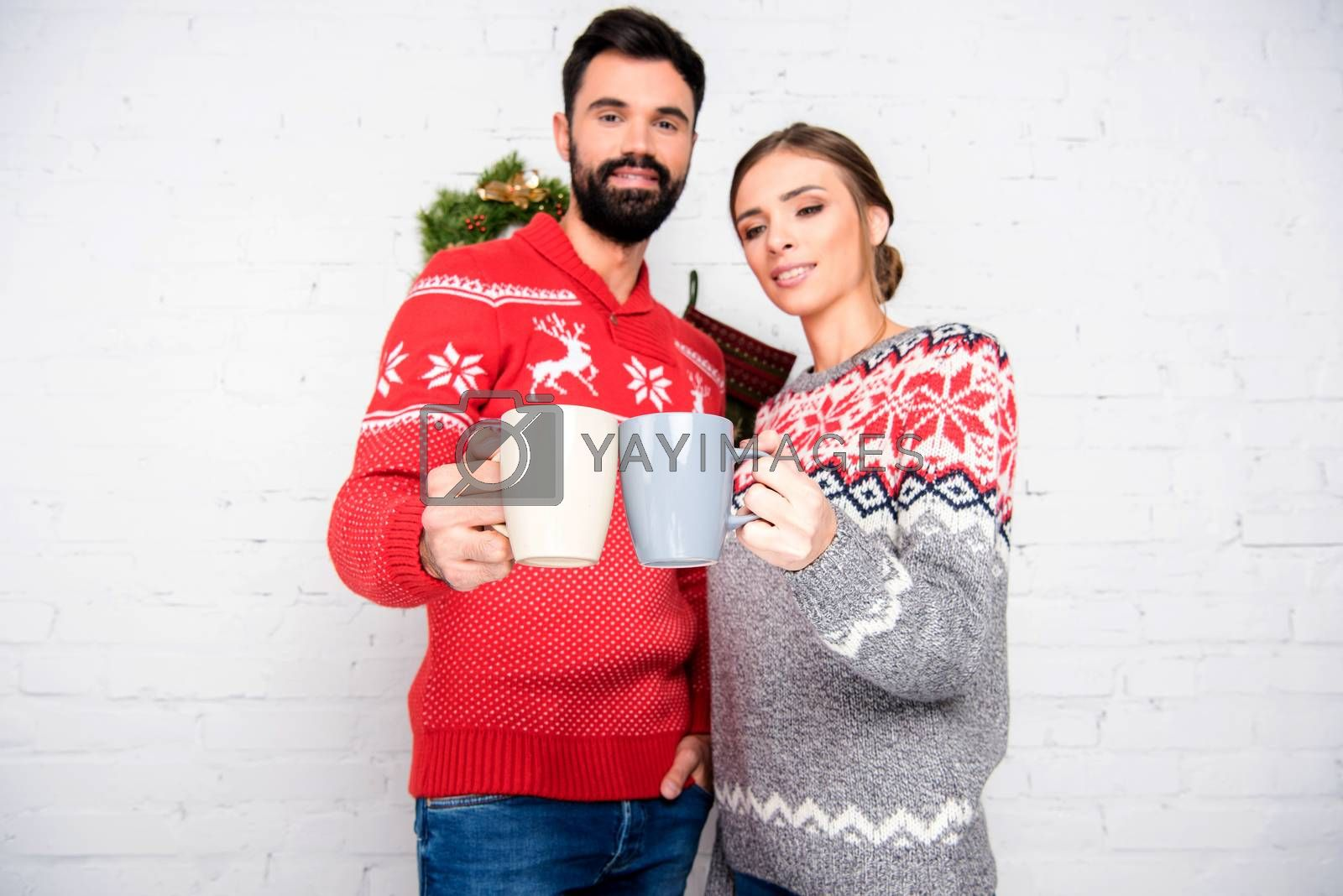Happy couple wearing christmas sweaters, toasting with cups on light