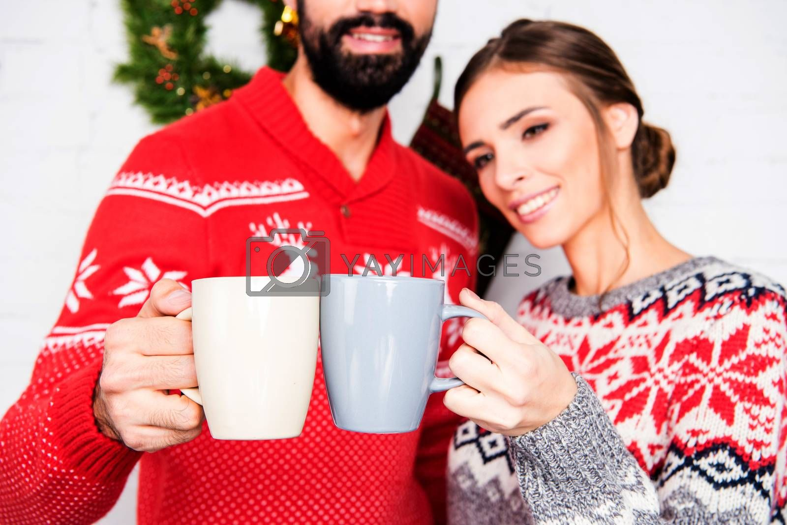 Happy couple wearing christmas sweaters, toasting with cups