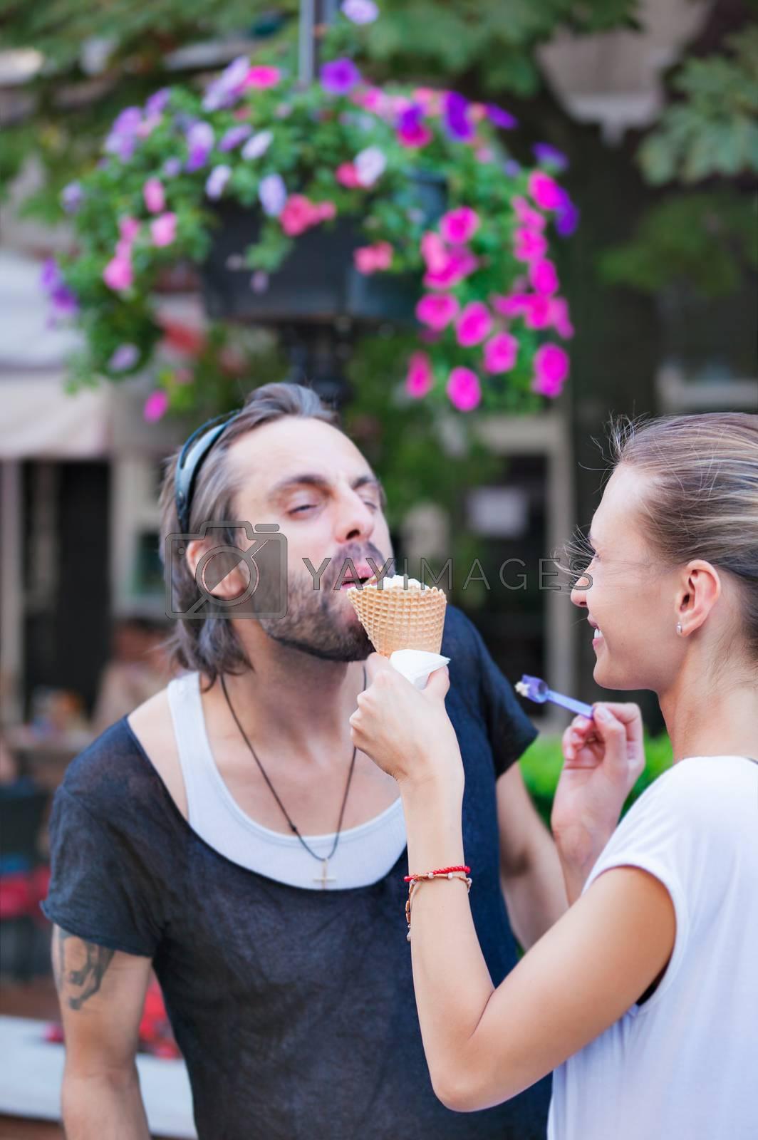 A female is feeding her boyfriend or husband with ice cream on the street.