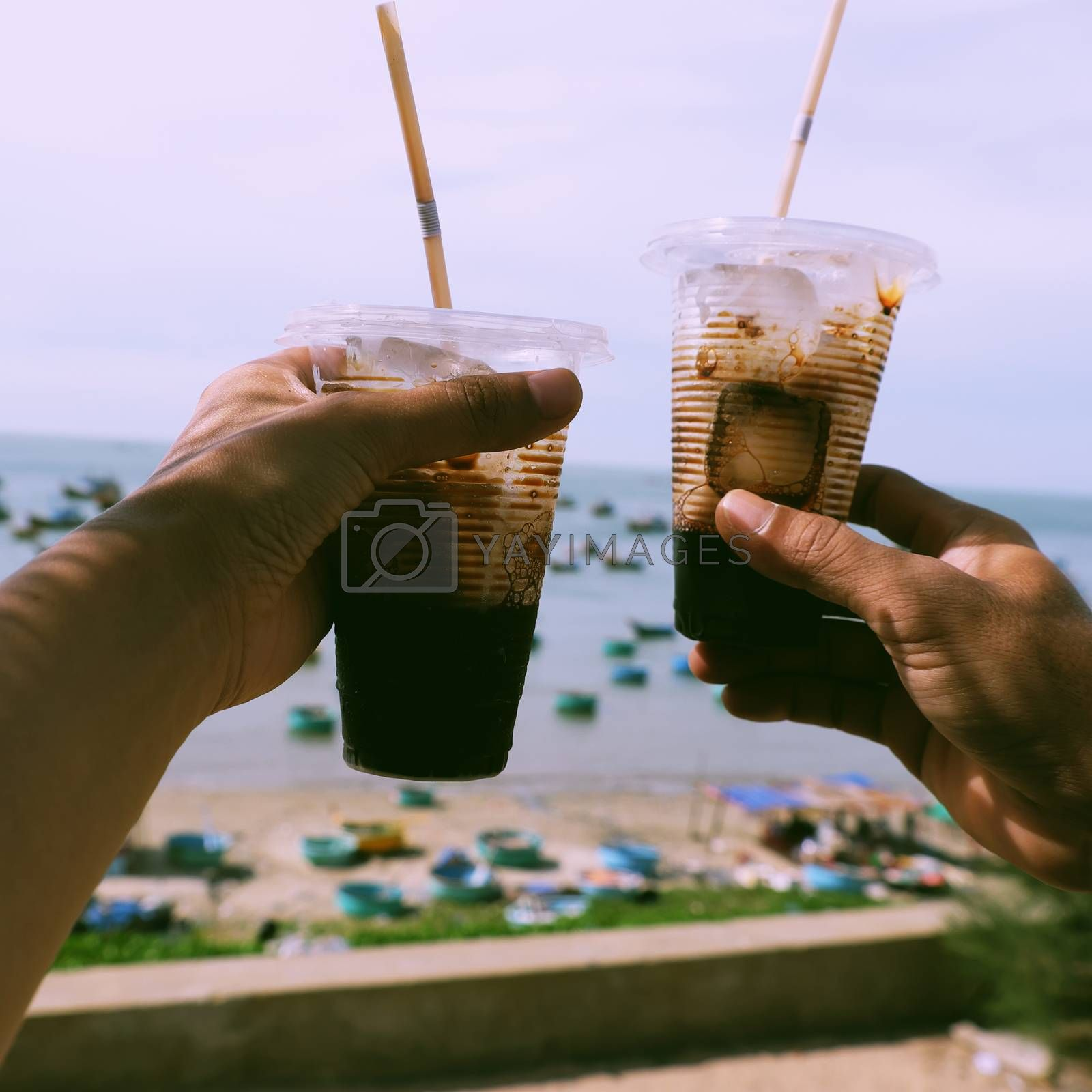 Couple hand hold coffee cup up to sky at beach in morning, quick cafe time on the way in summer journey to enjoy life