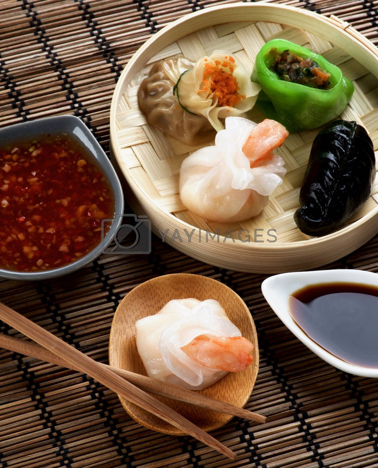 Assorted Dim Sum in Bamboo Steamed Bowl and Tori with Shrimp on Wooden Plate with Red Chili and Soy Sauces and Chopsticks closeup on Straw Mat background