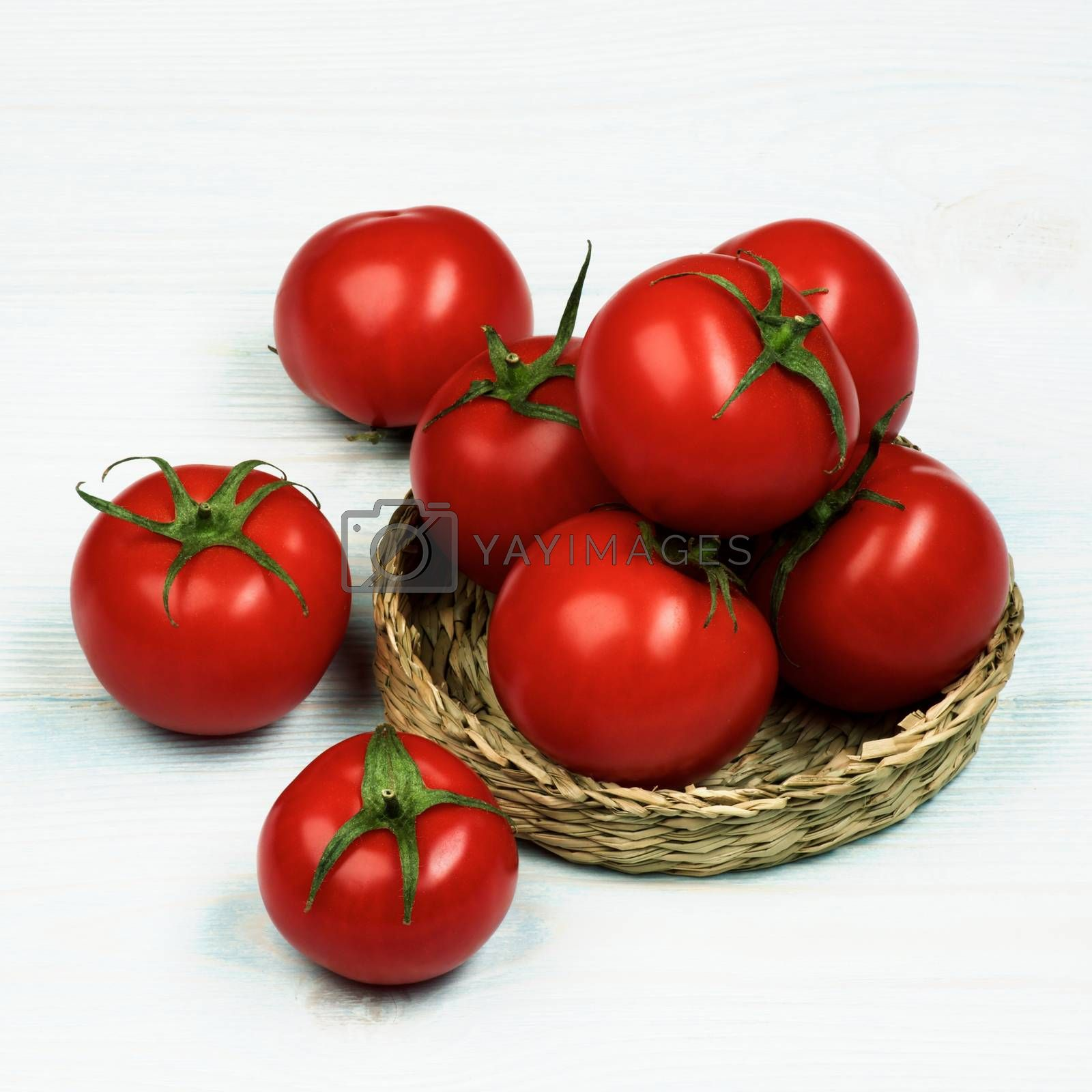 Arrangement of Ripe Raw Red Tomatoes with Stems in Wicker Plate closeup on Light Wooden background