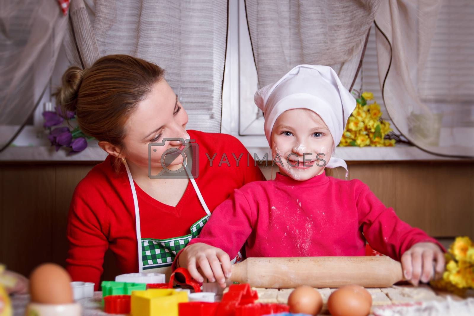 Cute girl rolling dough with her mother