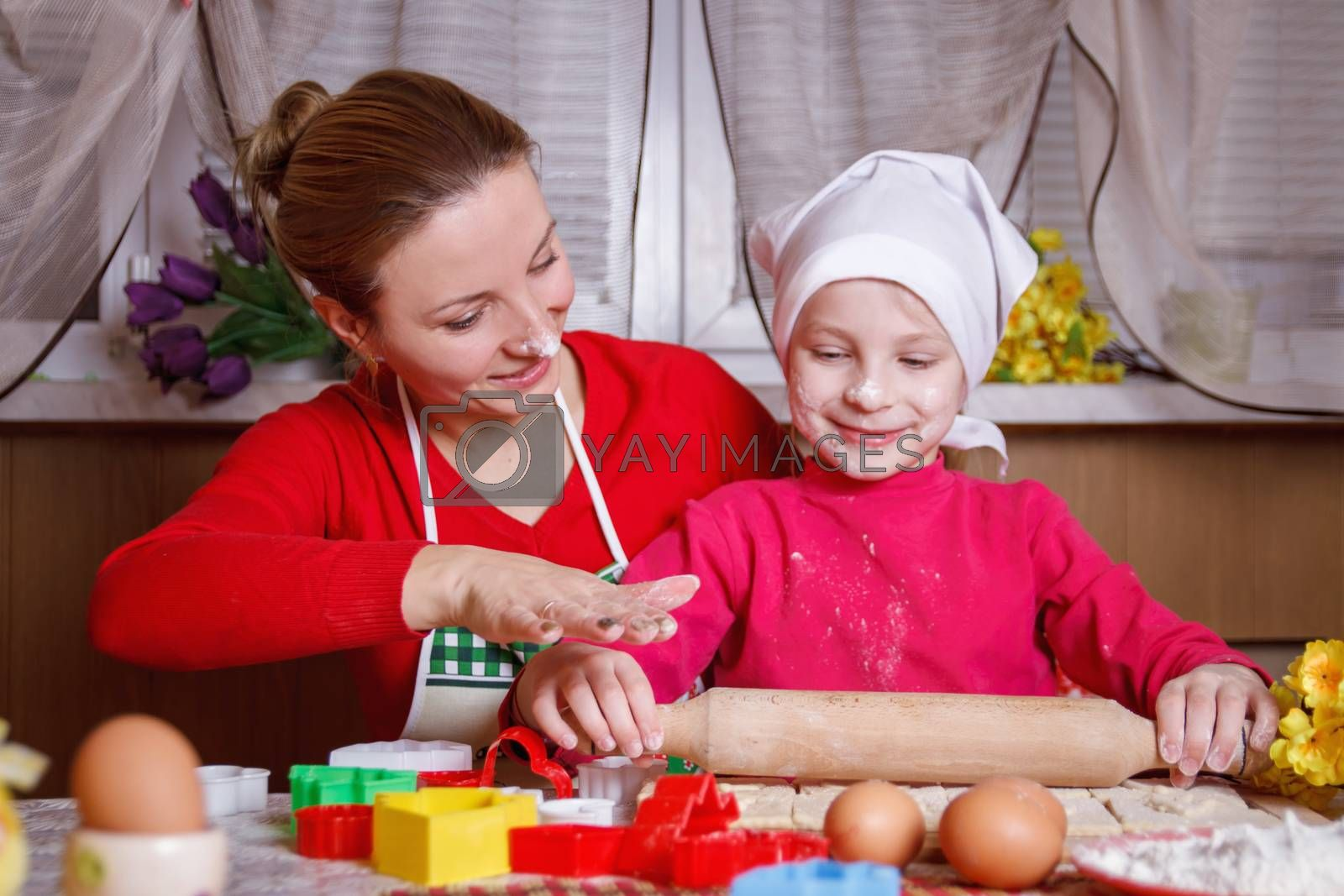 Cute girl rolling dough with her mother for bisquit