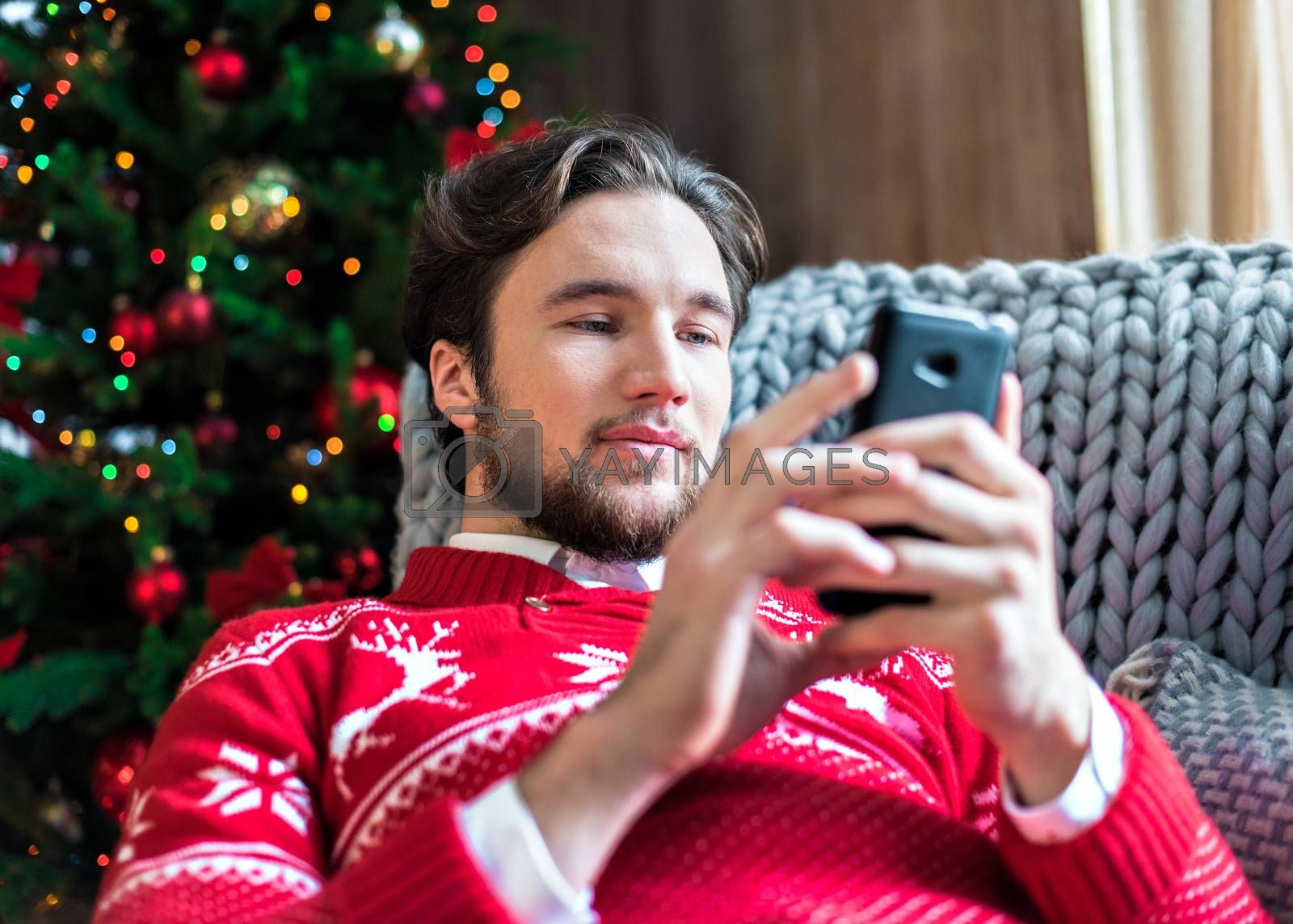 Smiling man lying on grey couch and using smartphone