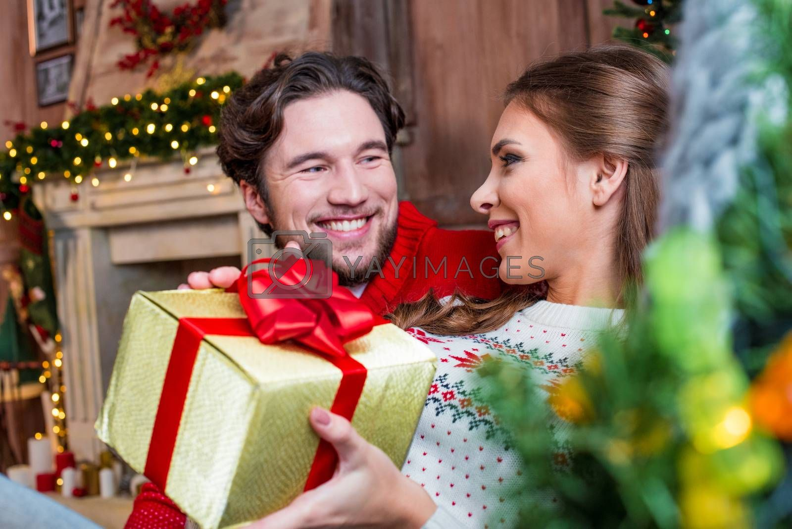 Happy young couple with christmas present looking at each other