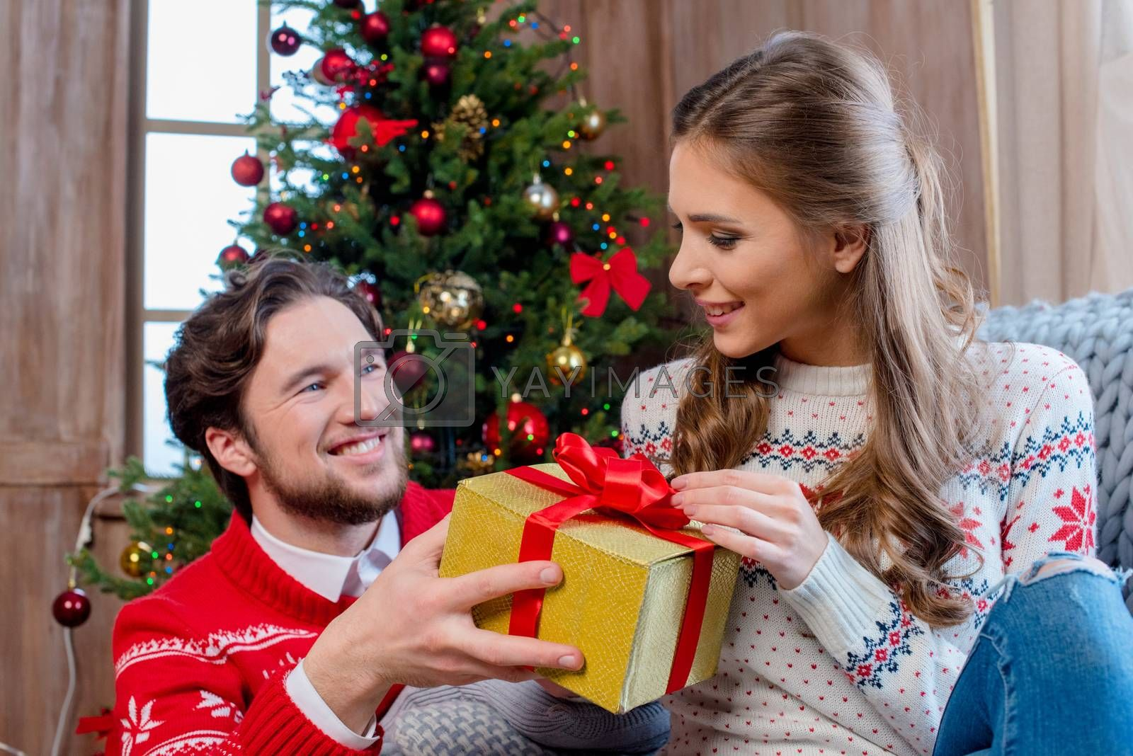 Happy young couple with christmas present