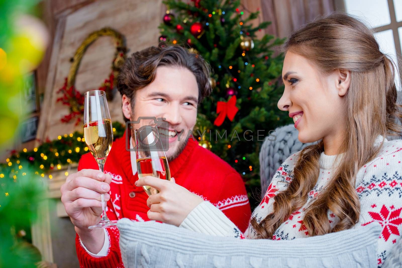 Happy couple looking at each other and toasting with champagne glasses at christmastime