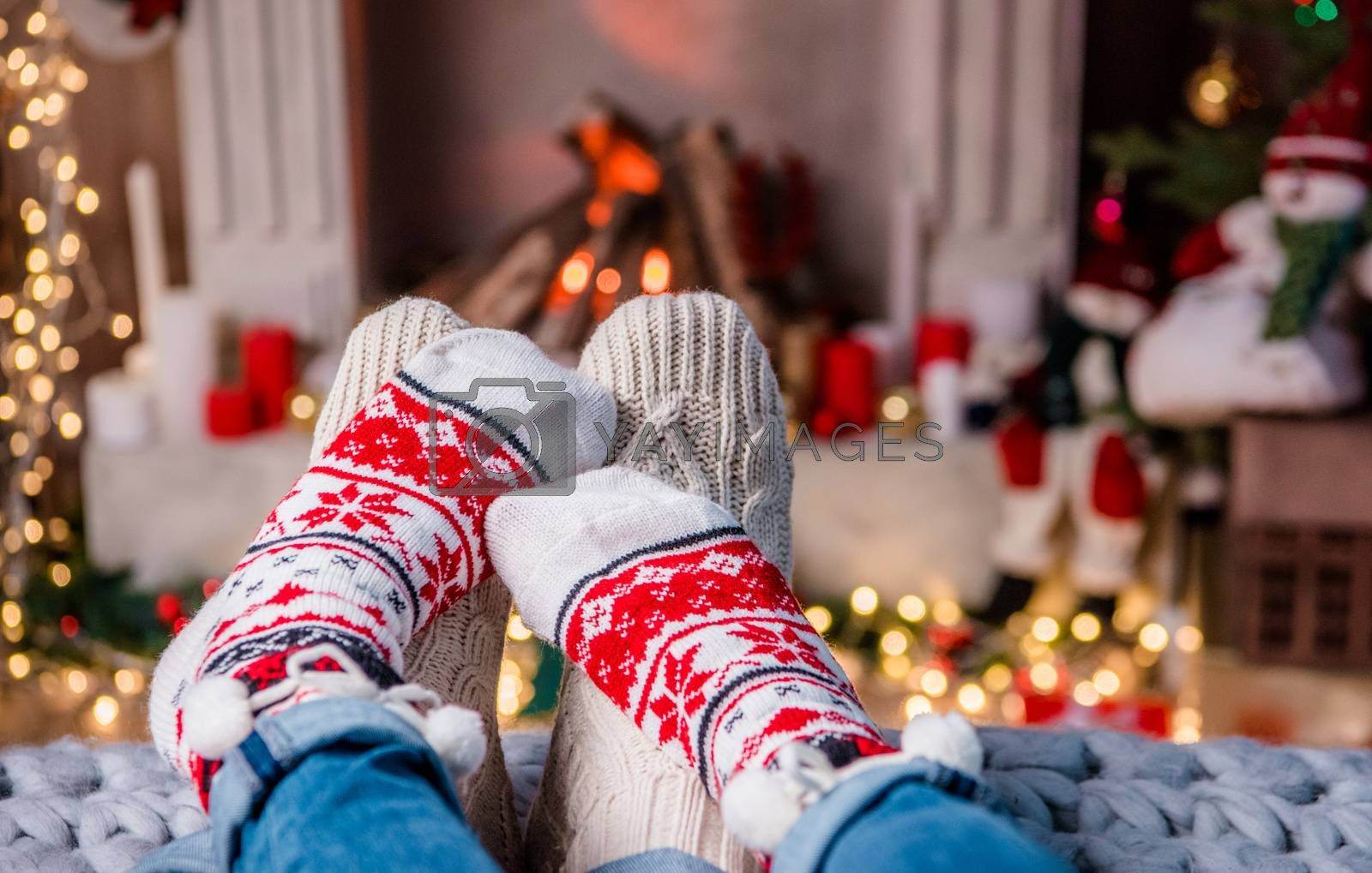 Legs in warm  socks of loving couple lying in front of fireplace