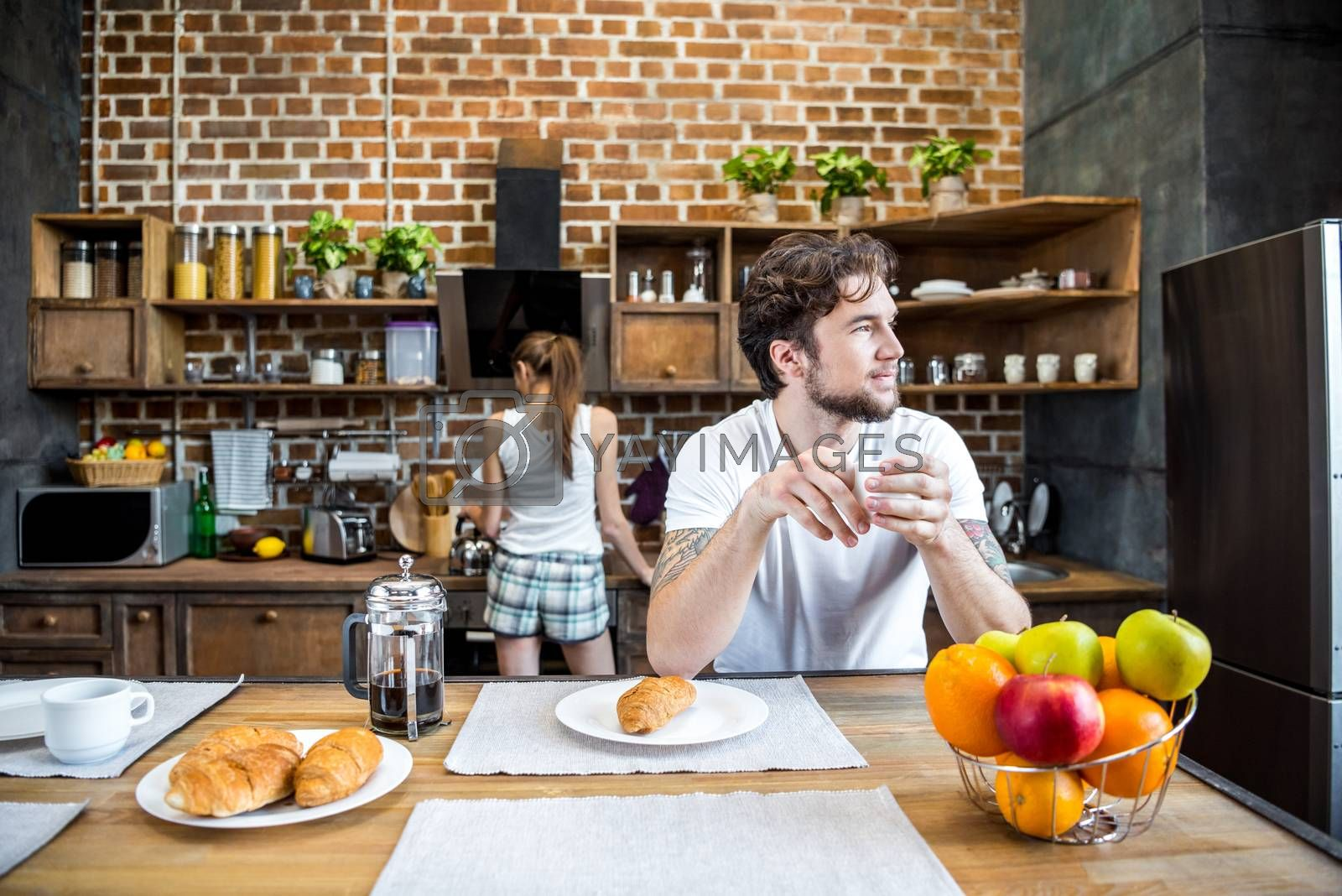 Smiling man in white t-shirt drinking coffee and looking away in kitchen