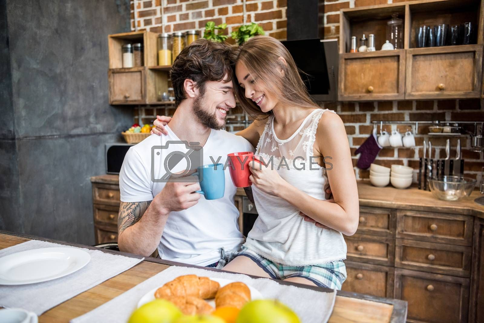 Happy young couple drinking tea at breakfast in kitchen