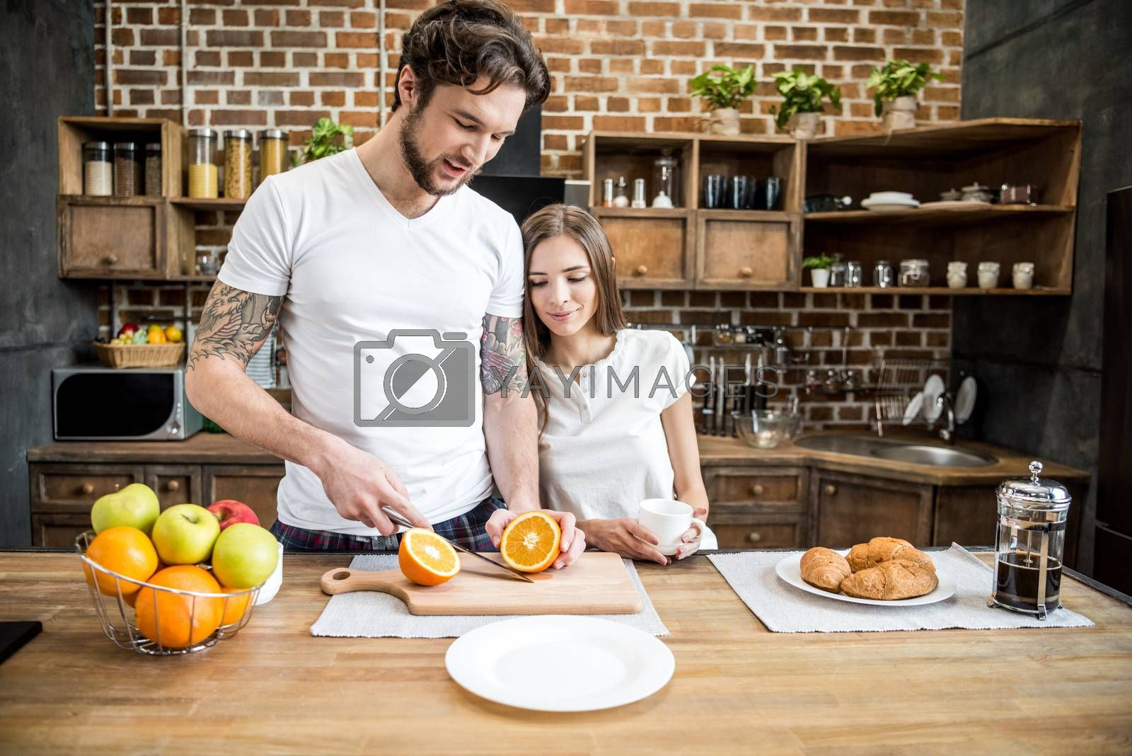 Attractive woman with coffee cup looking at young man cutting orange in kitchen