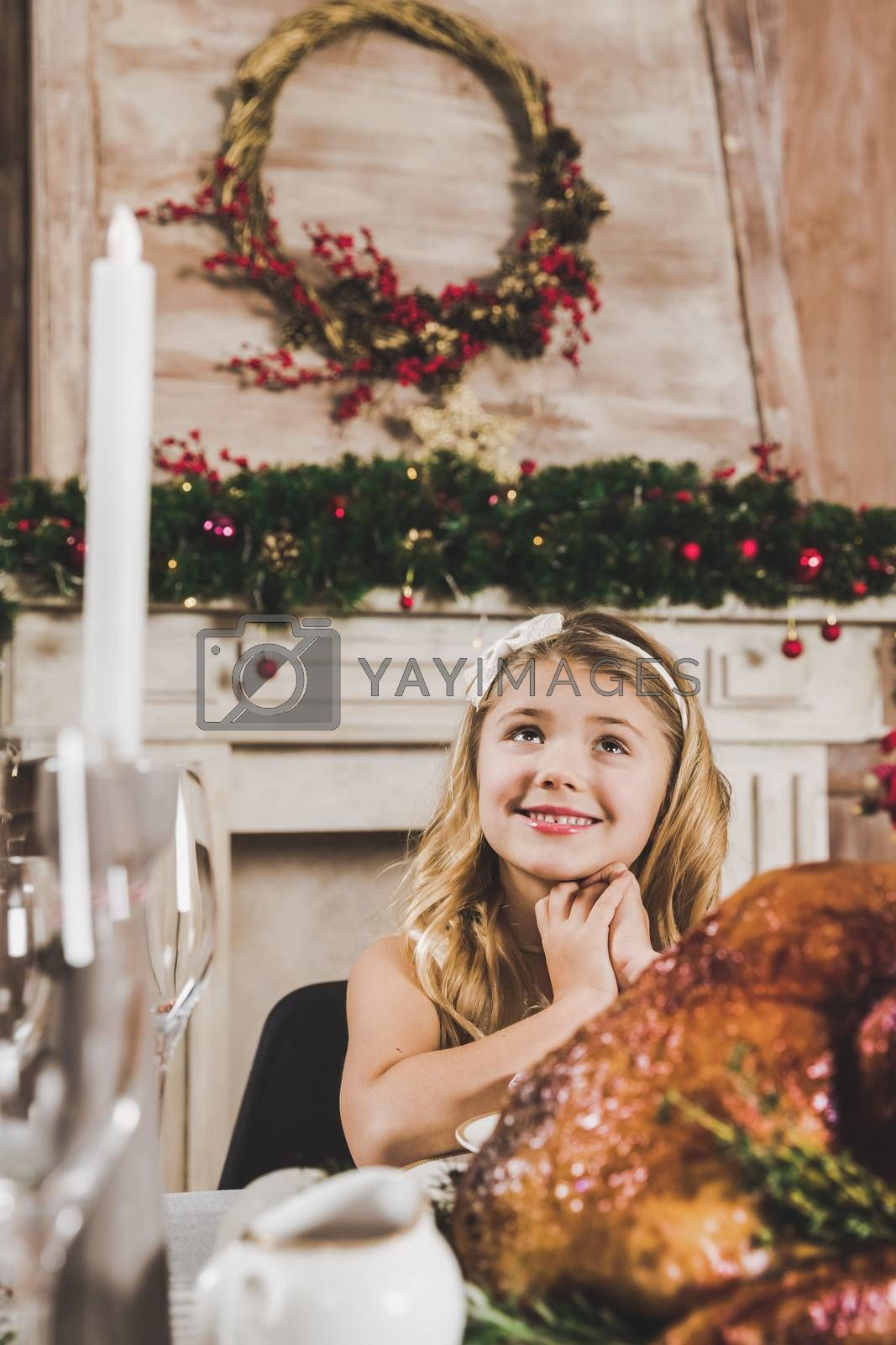 Cute smiling girl sitting at holiday table and looking up at Christmas time