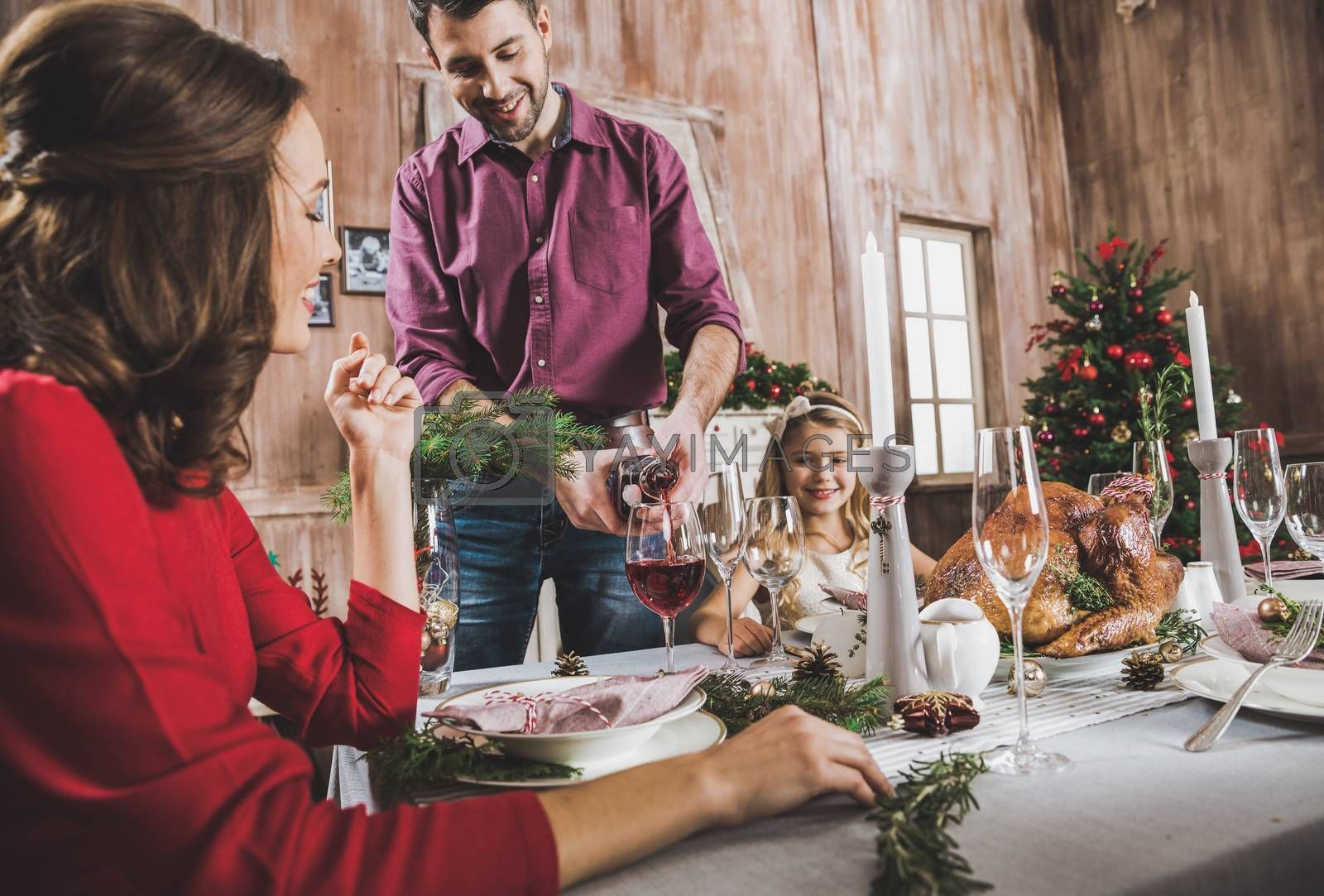 Happy family sitting at holiday table at Christmas time