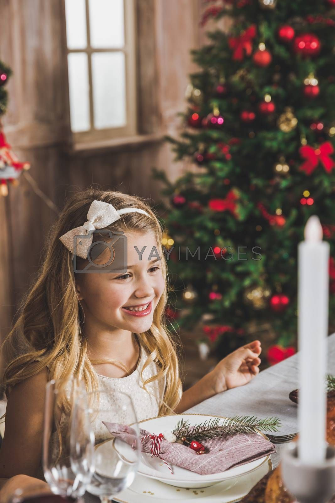 Cute smiling girl sitting at holiday table at Christmas time