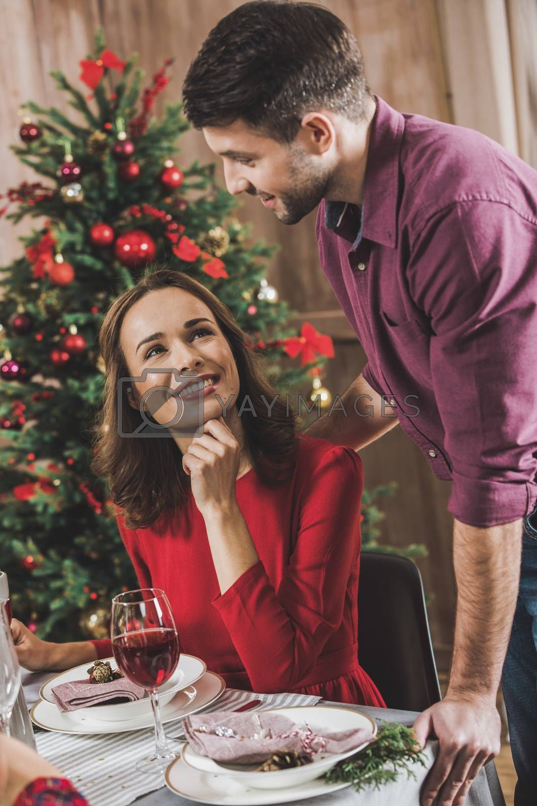 Smiling young couple at holiday table at Christmas eve