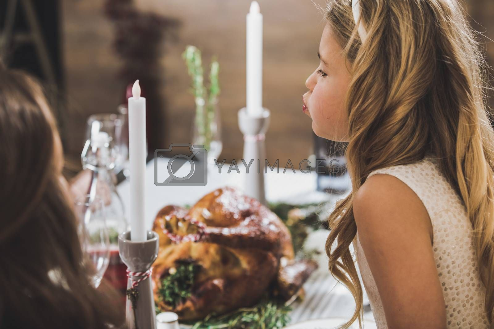 Side view portrait of cute little girl sitting at holiday table and looking at roasted turkey