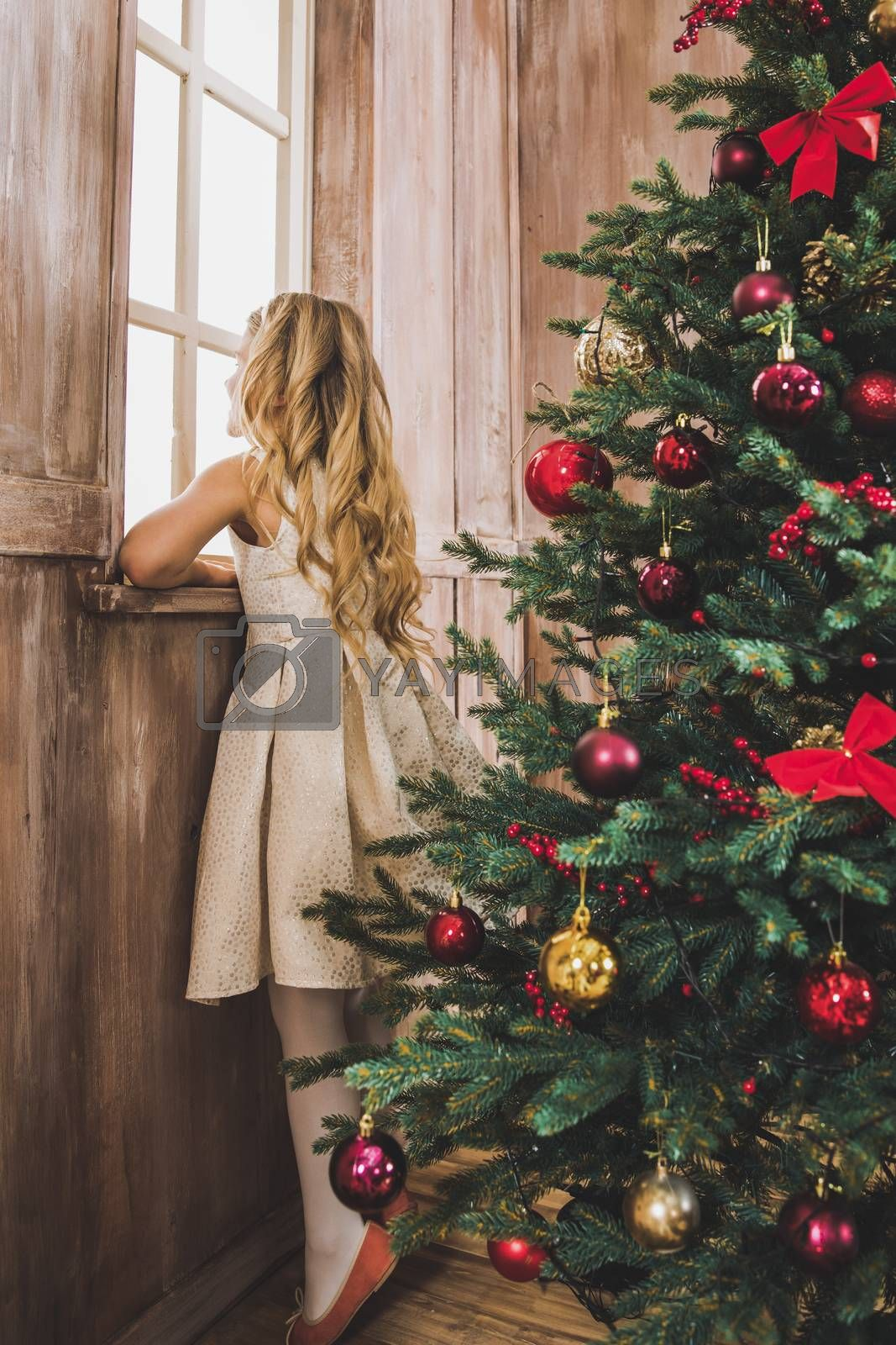 Cute little girl standing near Christmas tree and looking at window