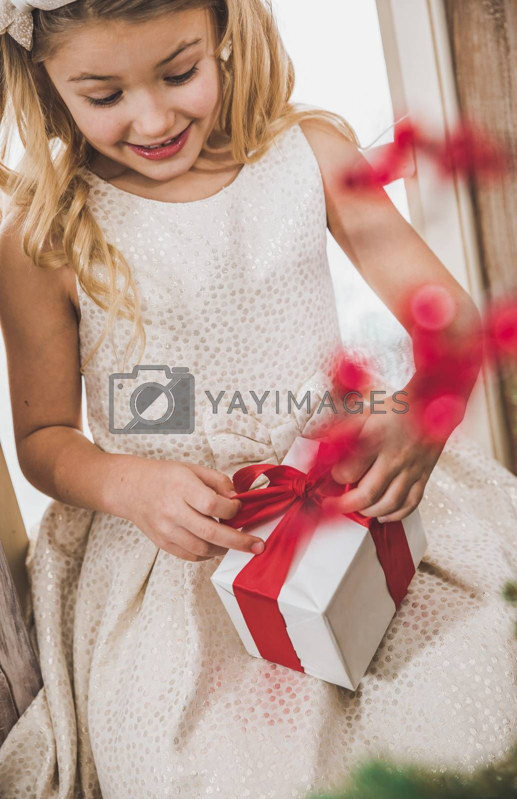 Portrait of cute smiling girl opening gift box