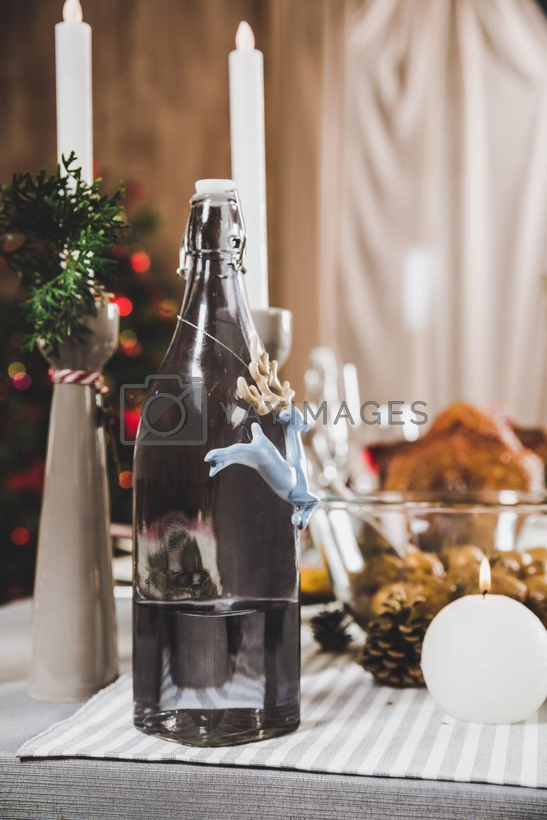 Close-up view of decorated bottle and Christmas decorations with burning candles on festive table