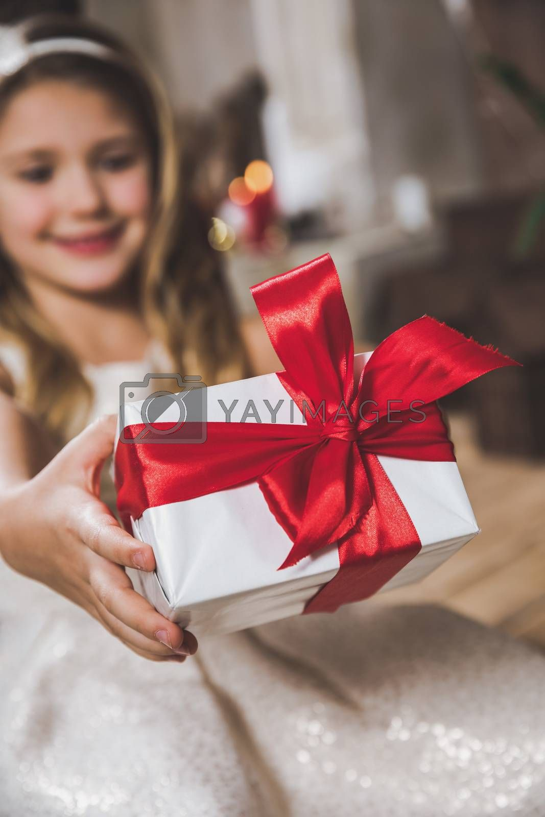 Close-up view of cute smiling girl holding gift box with red ribbon and bow