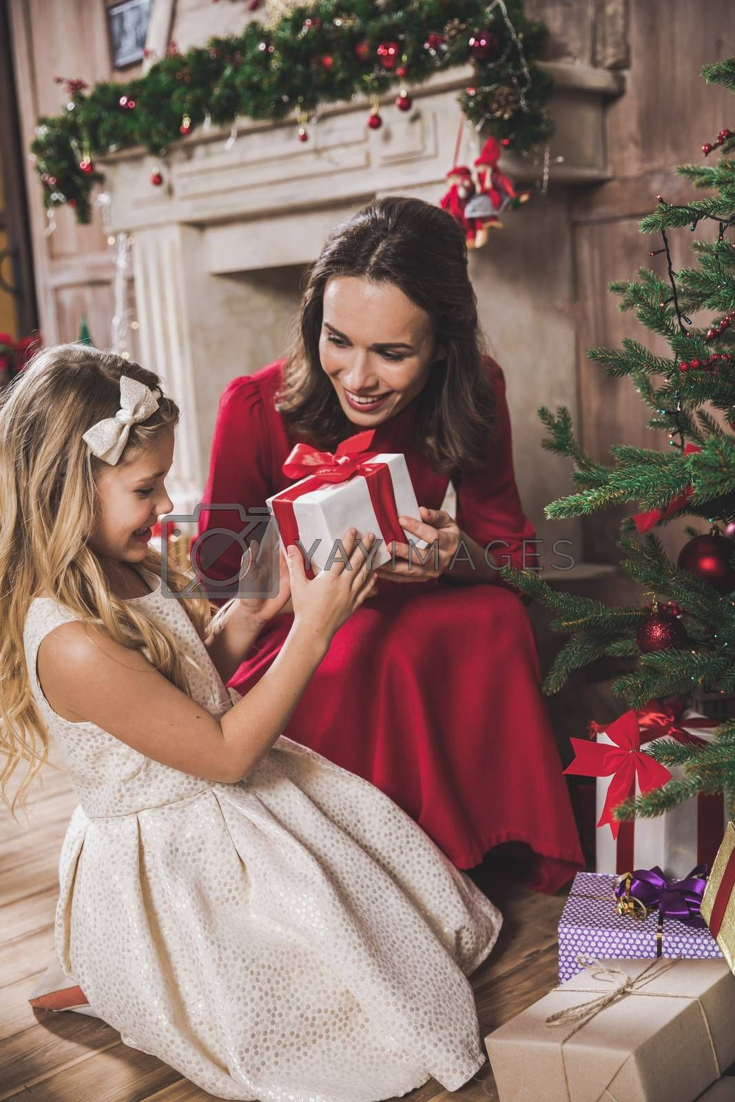 Happy mother giving Christmas present to cute smiling daughter
