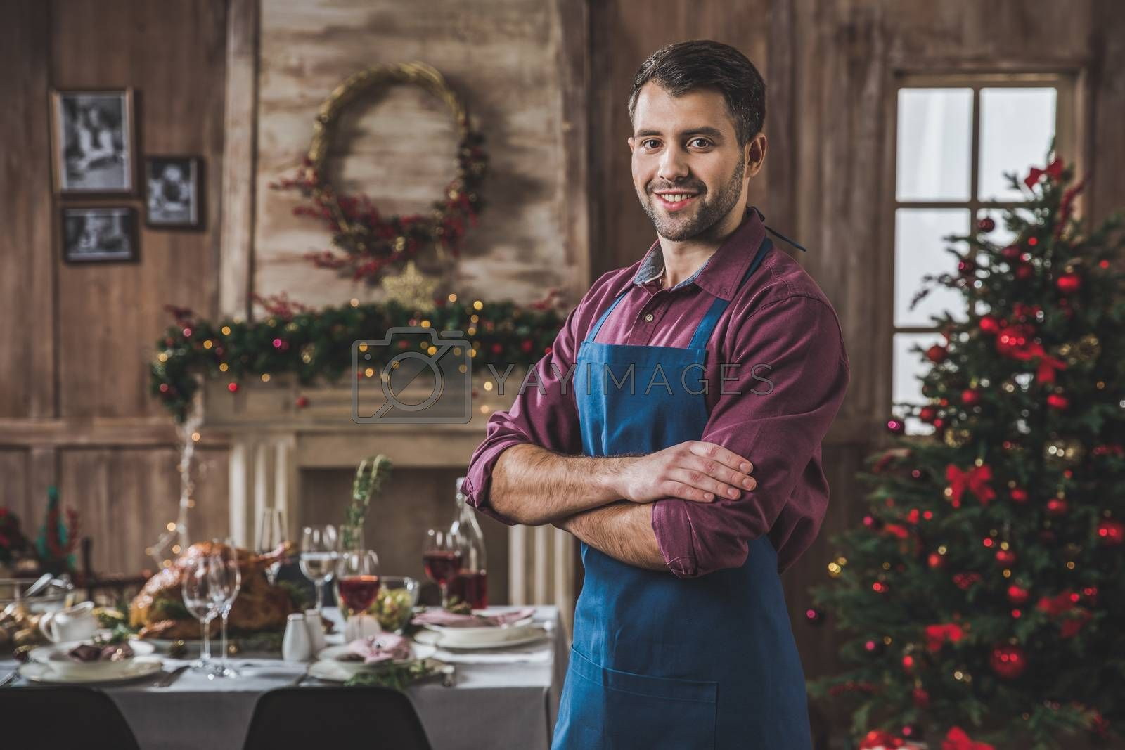 Smiling man in blue apron standing near Christmas table and looking at camera