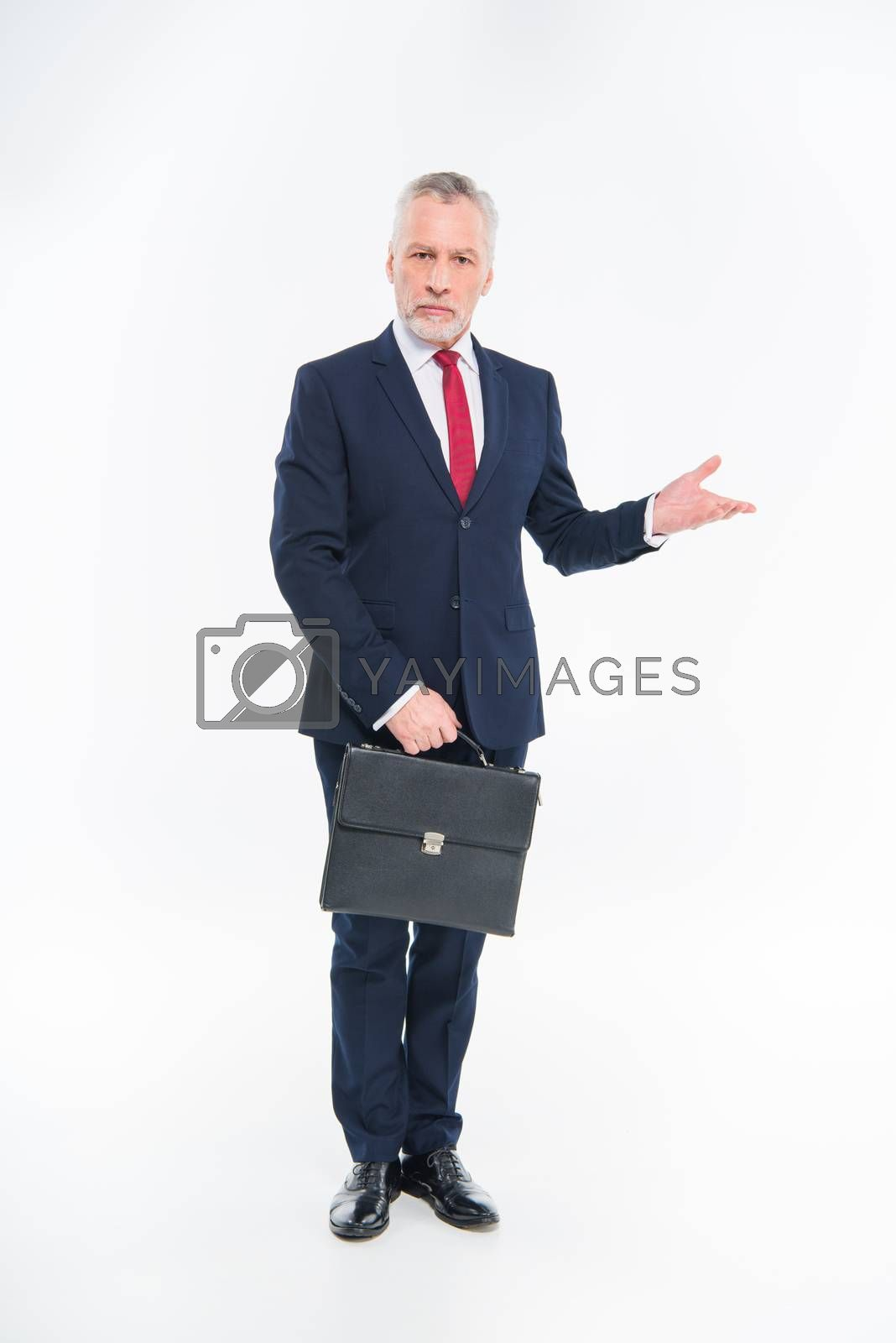 Mature businessman holding briefcase and gesturing with hand