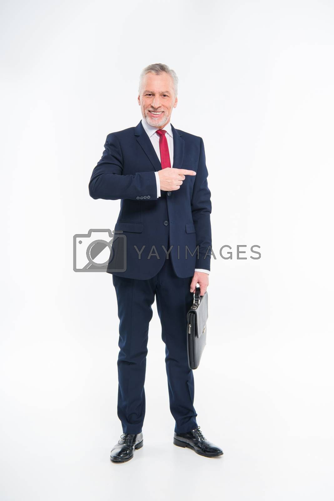 Royalty free image of Smiling businessman pointing with finger  by LightFieldStudios