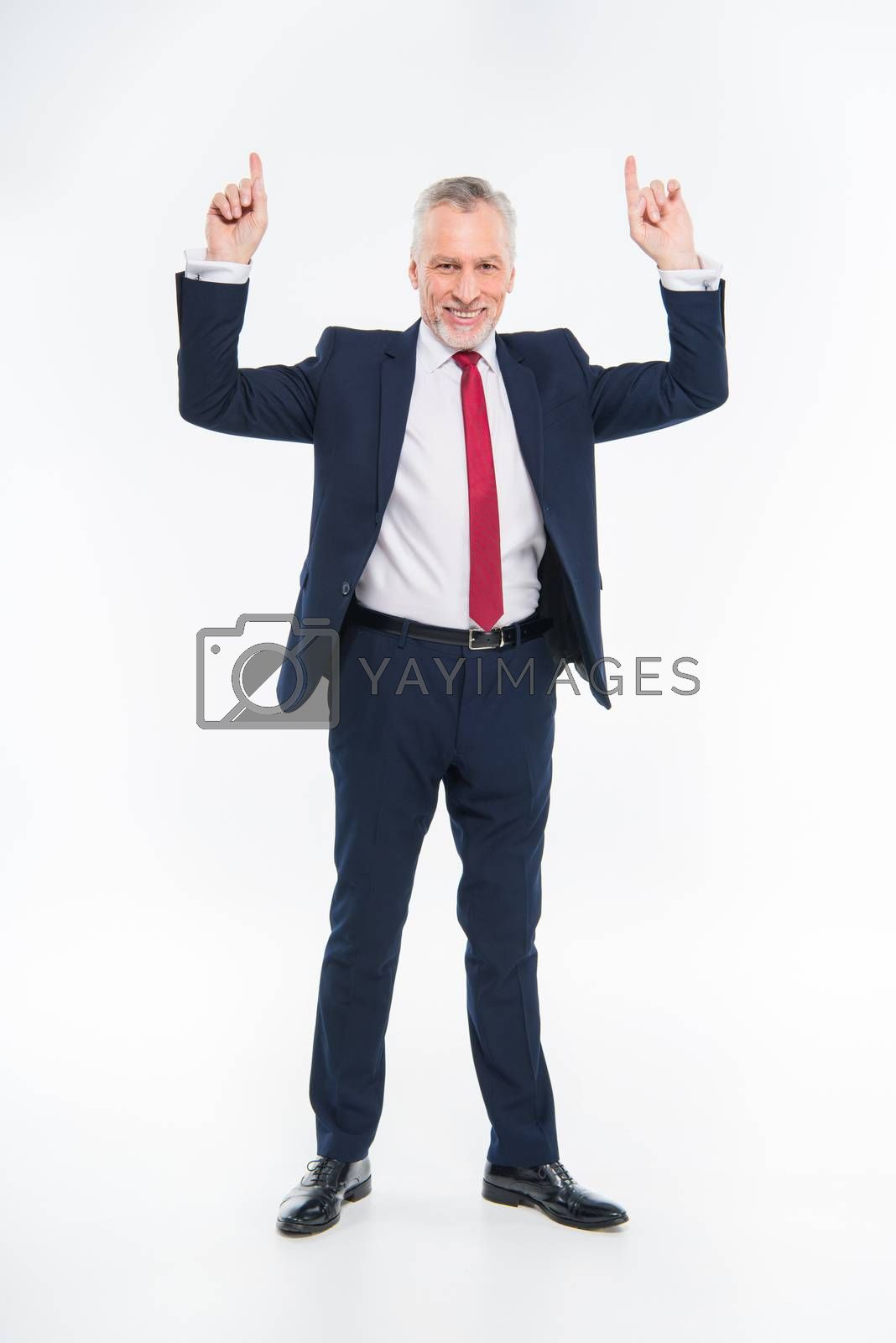 Smiling mature businessman pointing up with fingers on white