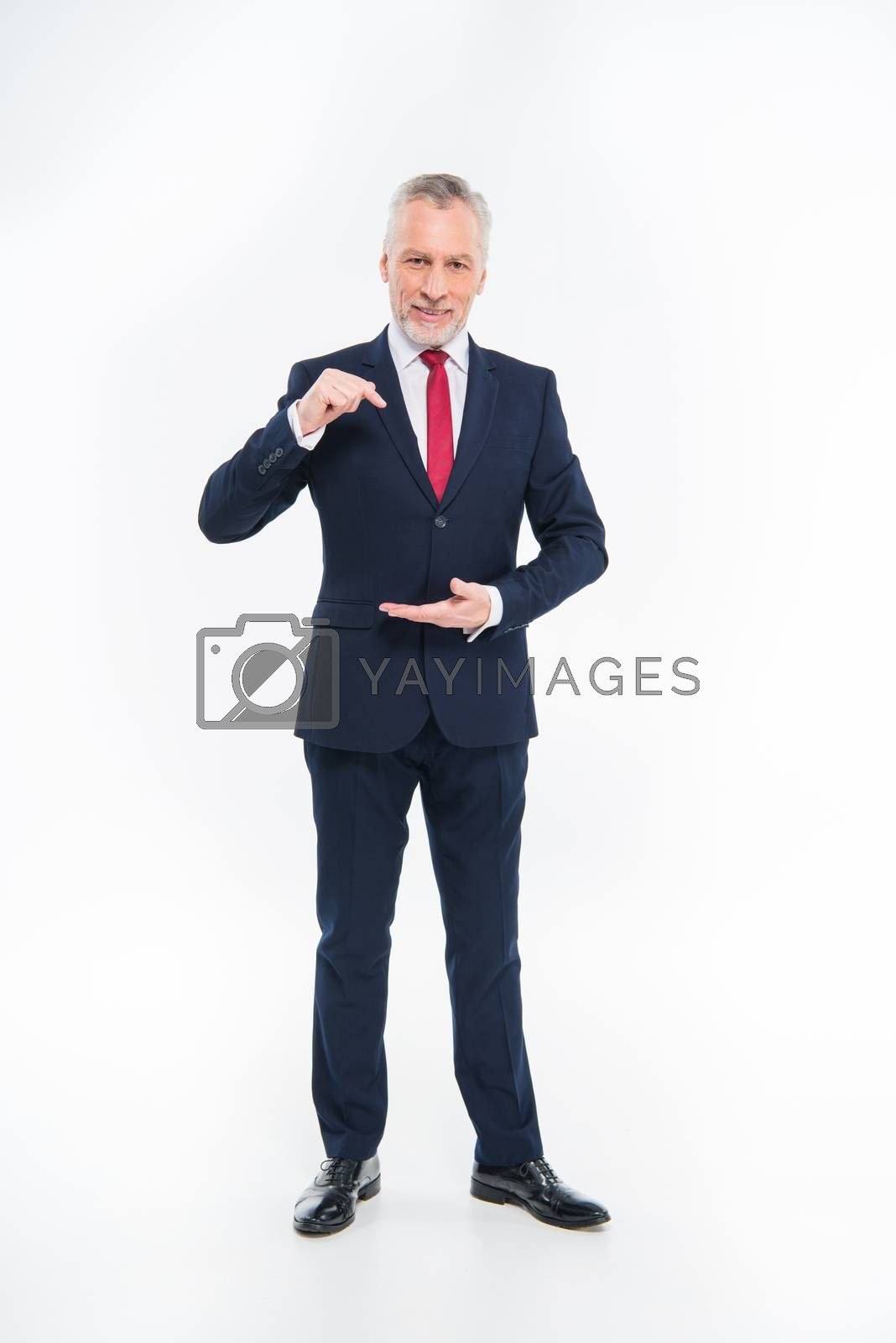 Handsome mature businessman in suit gesturing and pointing with finger