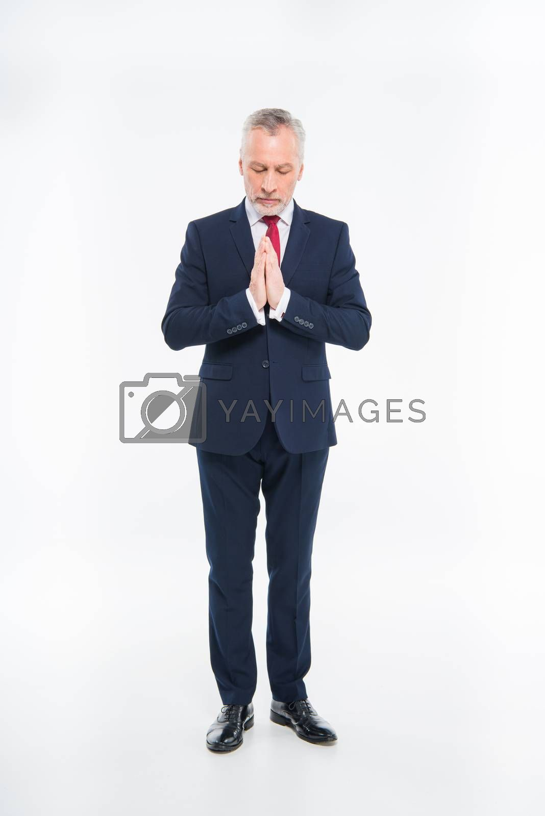 Royalty free image of Mature businessman praying by LightFieldStudios