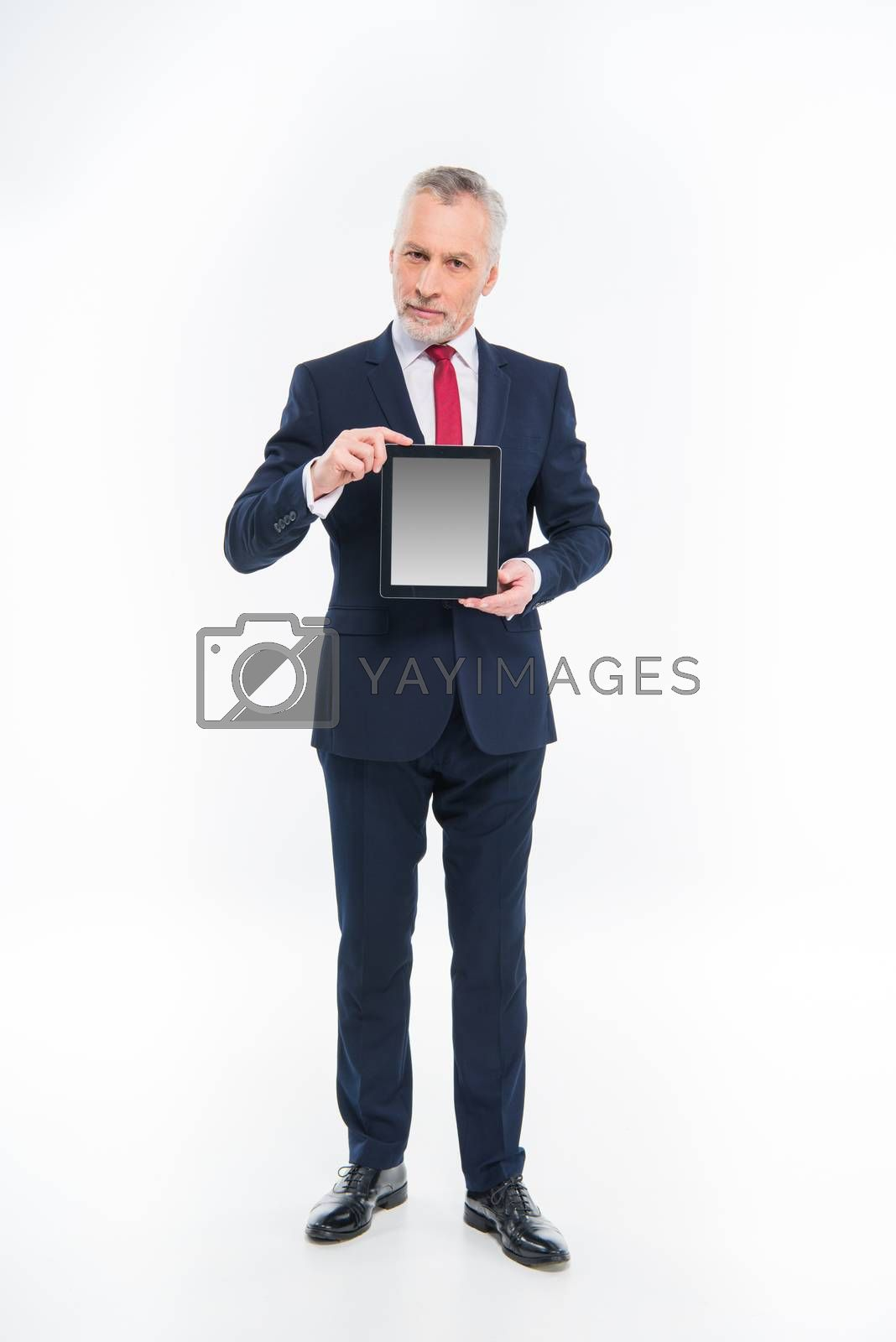 Full length portrait of businessman holding digital tablet and looking at camera