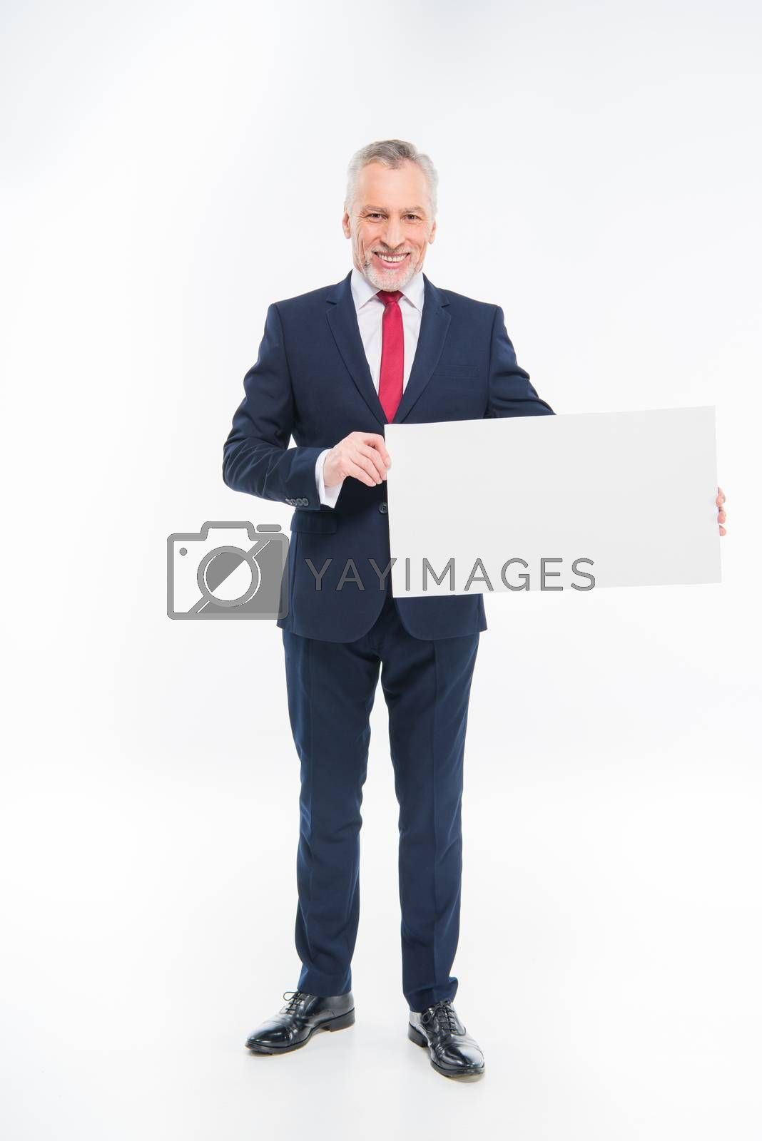 Royalty free image of Businessman holding blank card  by LightFieldStudios