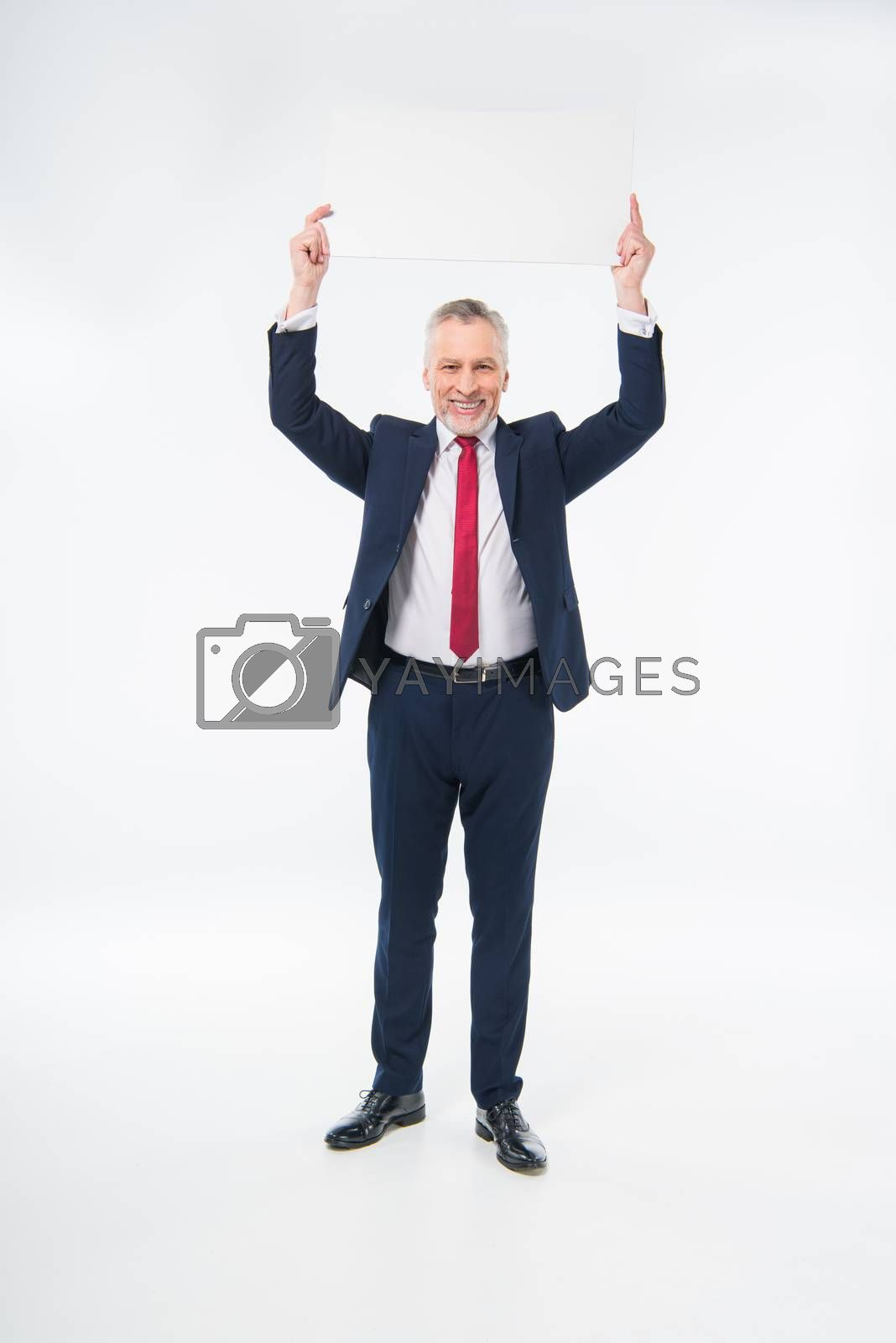 Handsome mature businessman holding blank card and smiling at camera on white