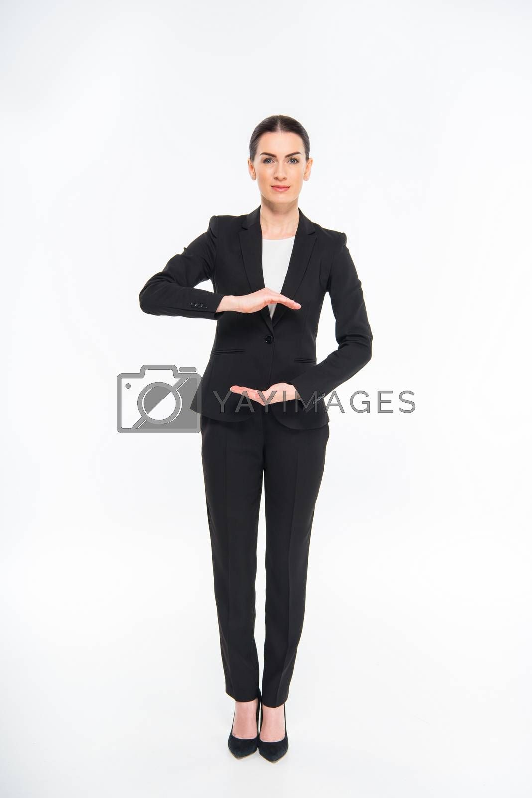 Attractive businesswoman gesturing with hands and looking at camera on white