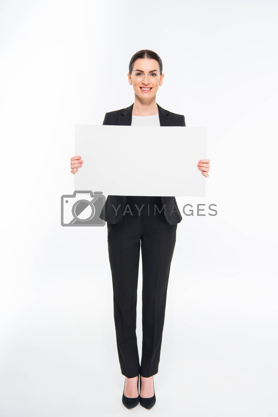 Smiling businesswoman holding blank white card and looking at camera