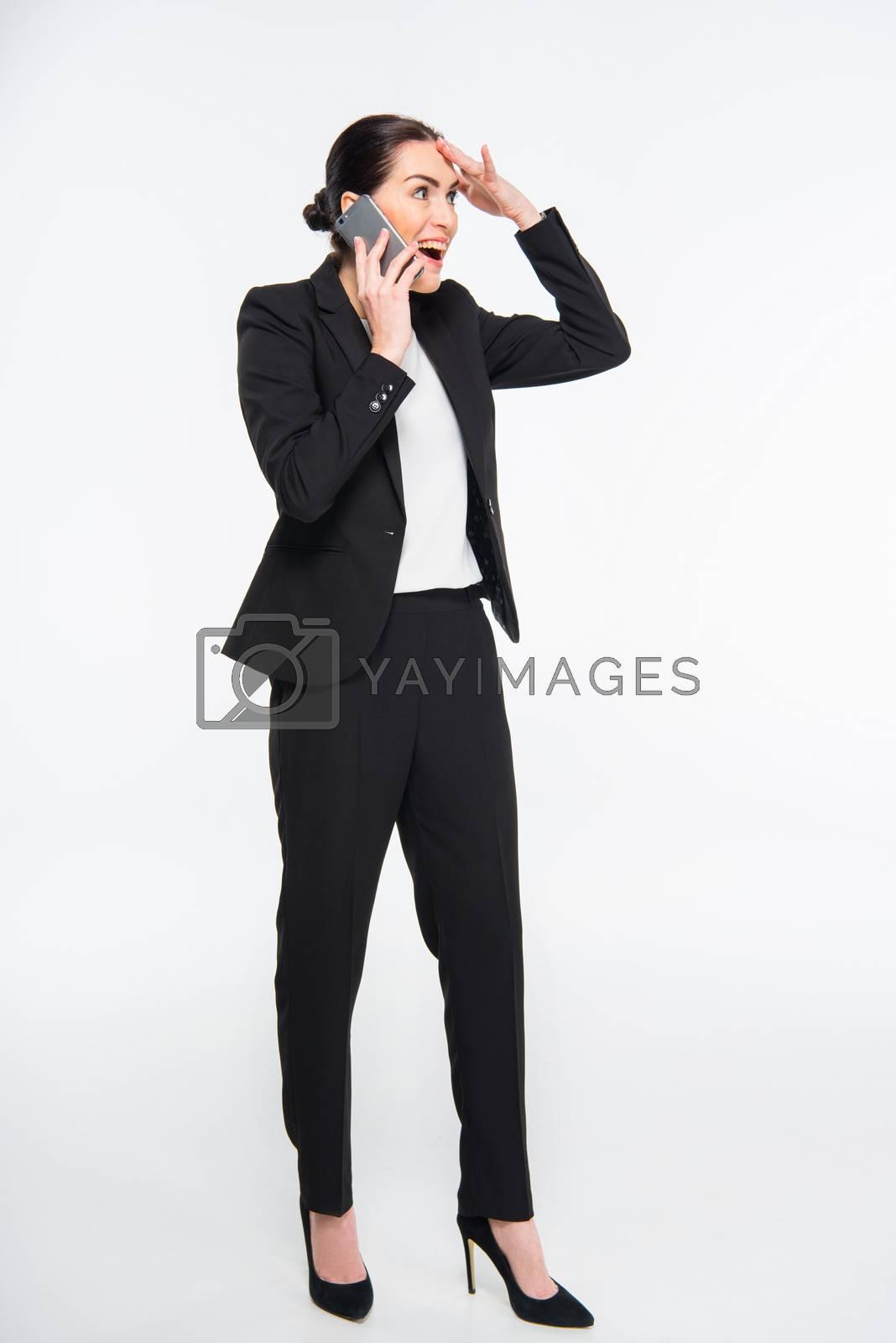 Surprised attractive businesswoman talking on smartphone