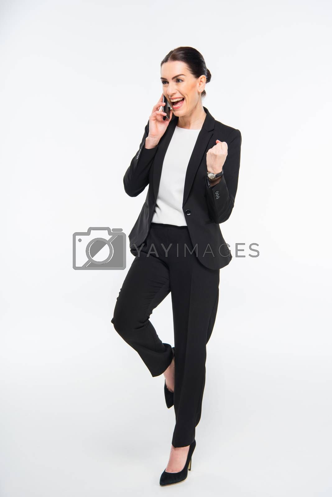 Excited professional businesswoman talking on smartphone on white