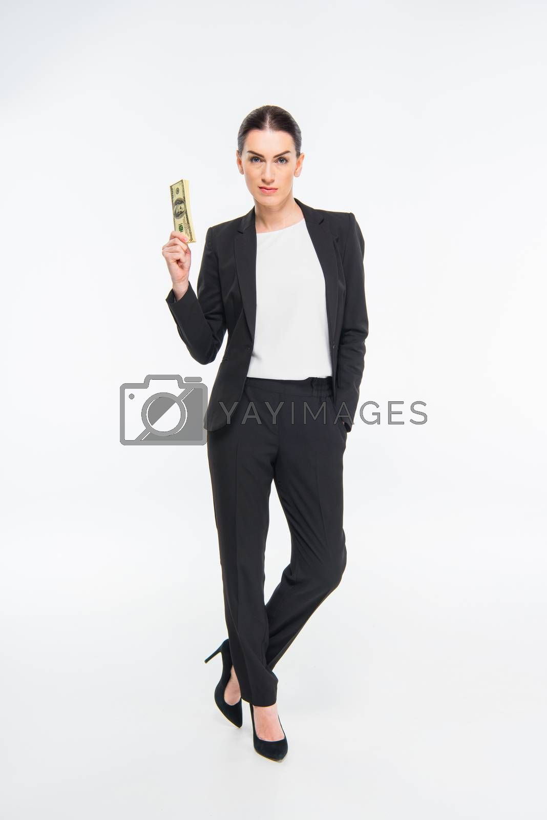 Professional young businesswoman holding dollar banknotes and looking at camera