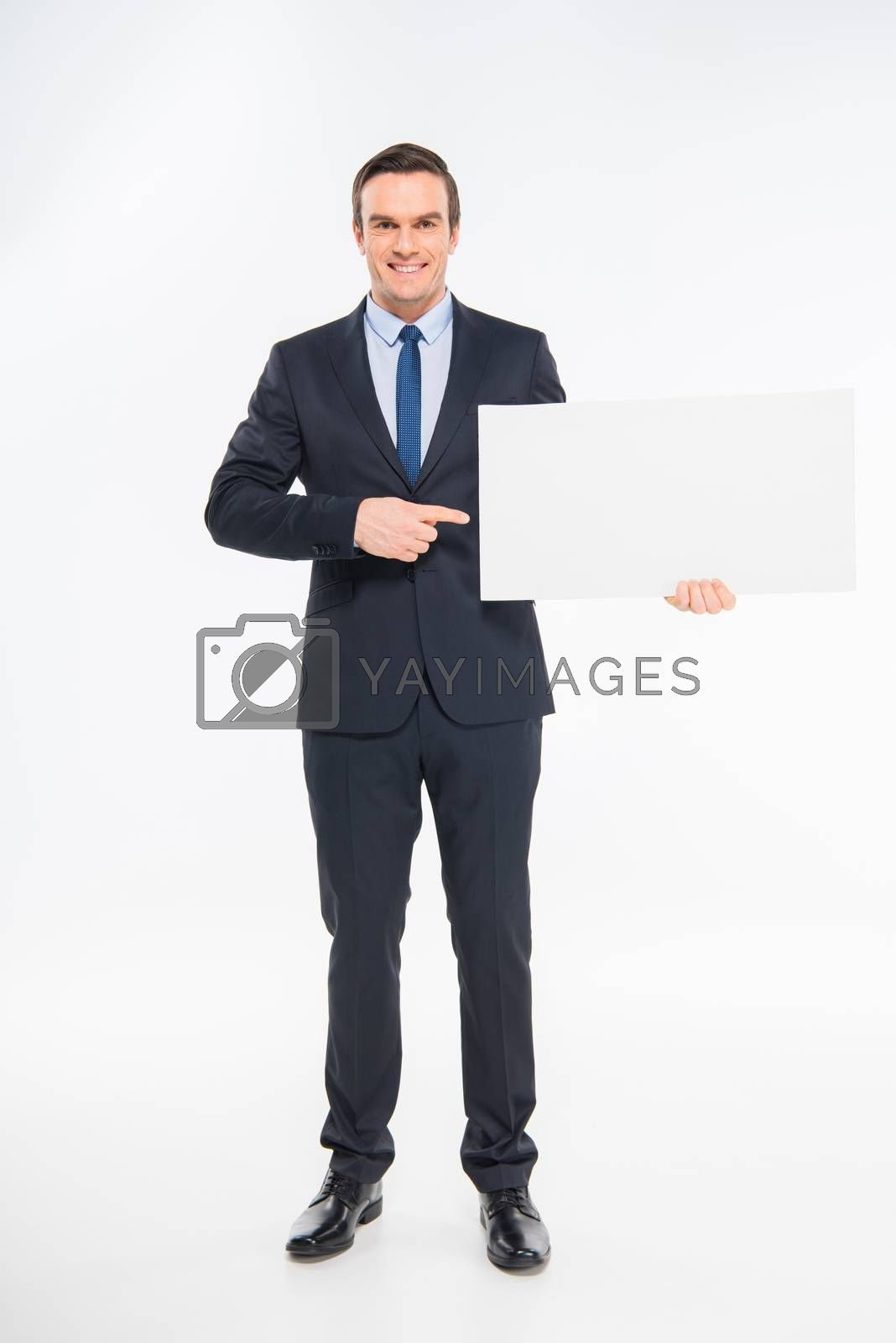 Smiling businessman holding blank card and pointing at copy space