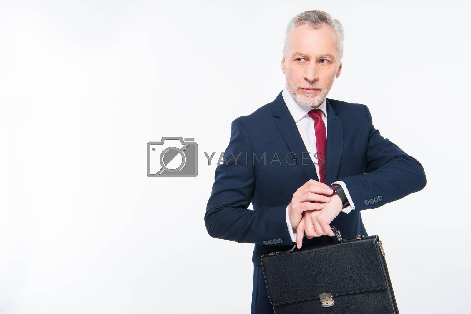 Handsome mature businessman with briefcase checking smartwatch