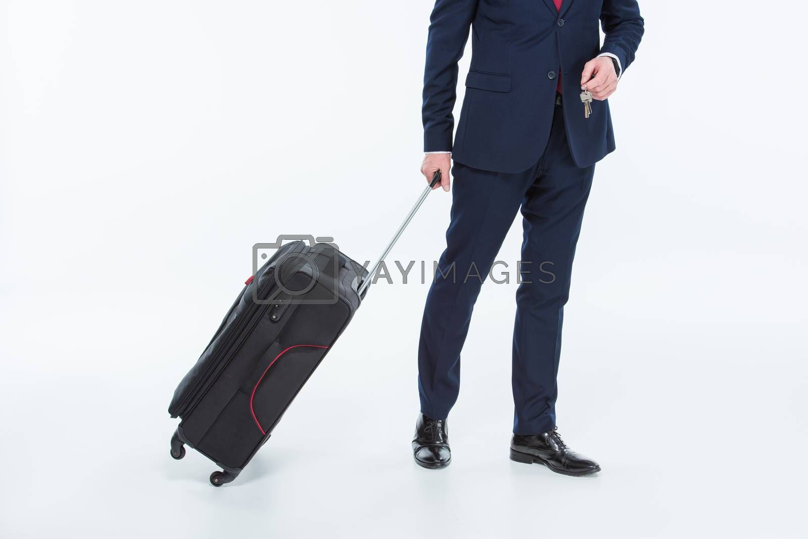 Partial view of businessman holding suitcase and keys