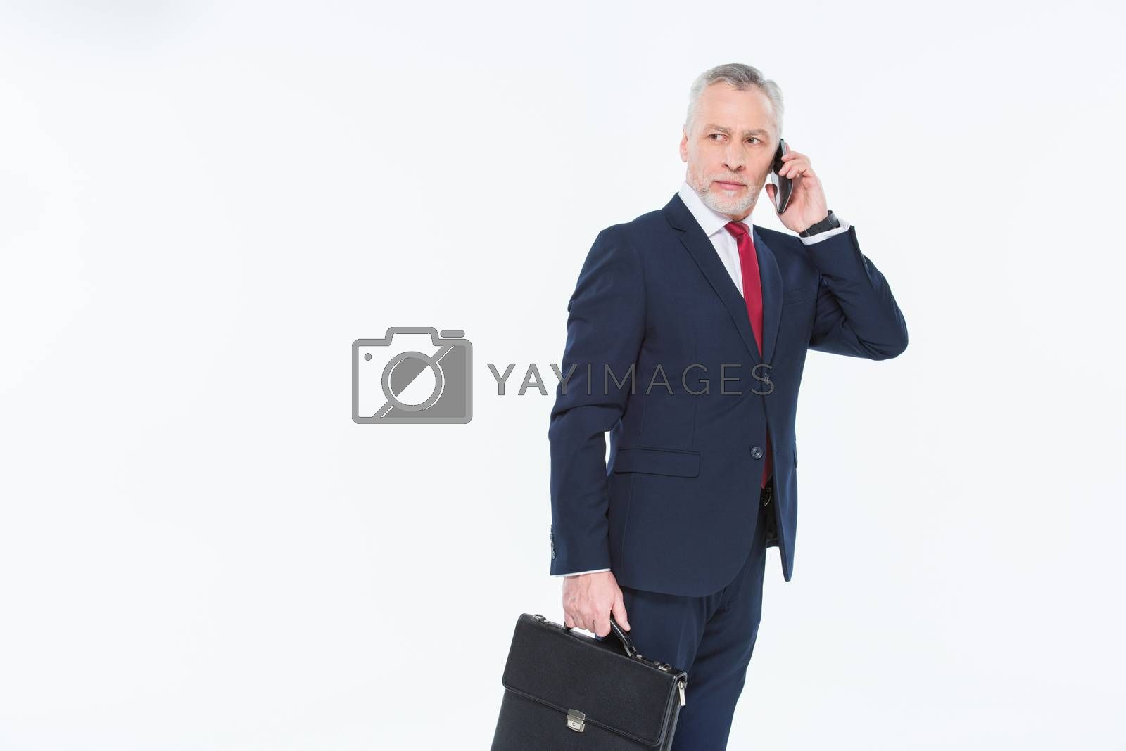 Handsome mature businessman holding briefcase and using smartphone